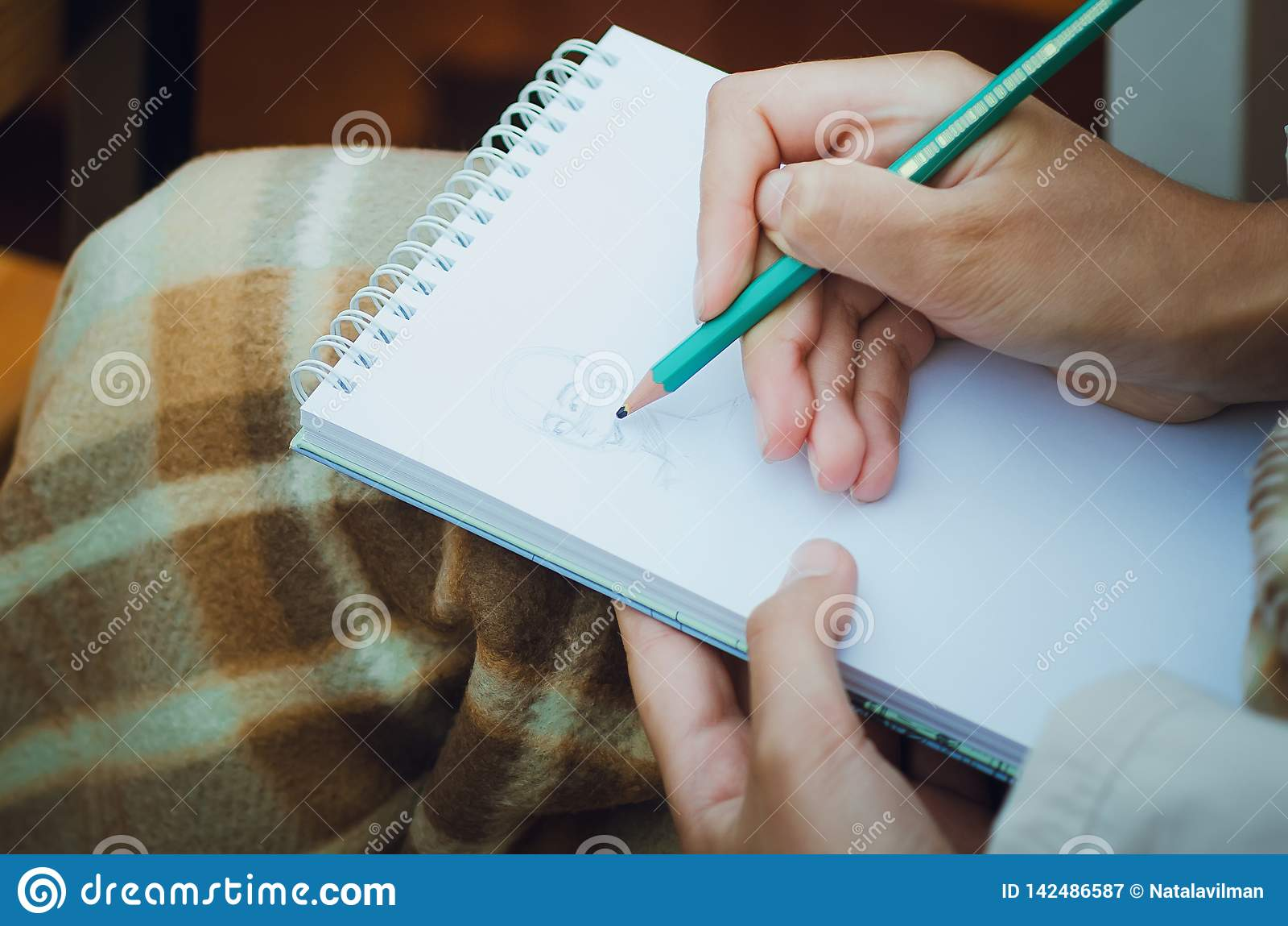 Plan rapproché de crayon et du dessin de participation de main dans le carnet