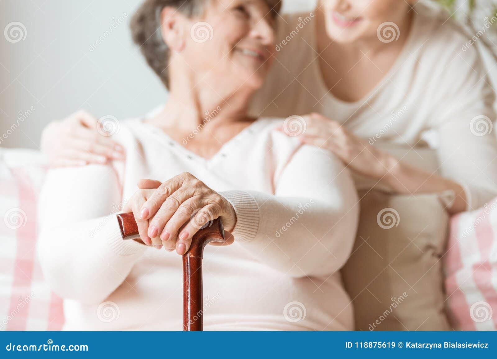 Plan rapproché de femme agée tenant le bâton de marche dans le h soignant