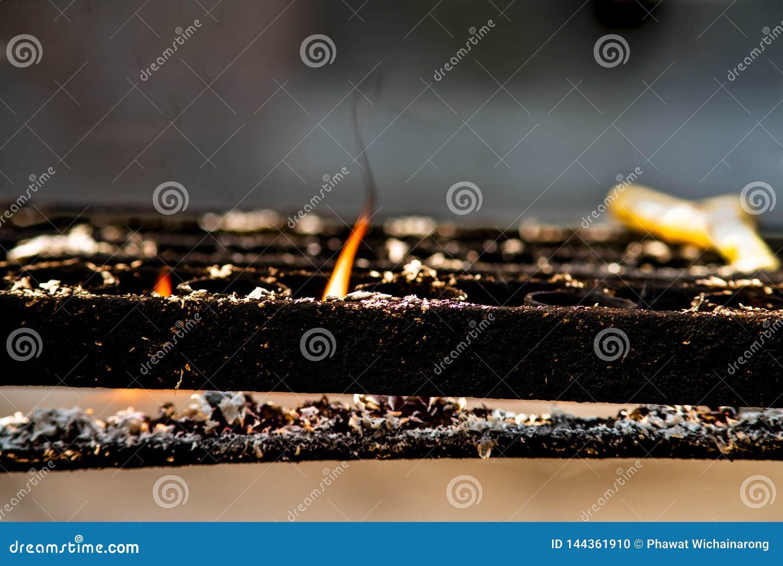 Plan rapproché de flamme orange de bougie brûlante sur le support noir de chandelier en métal à un temple bouddhiste