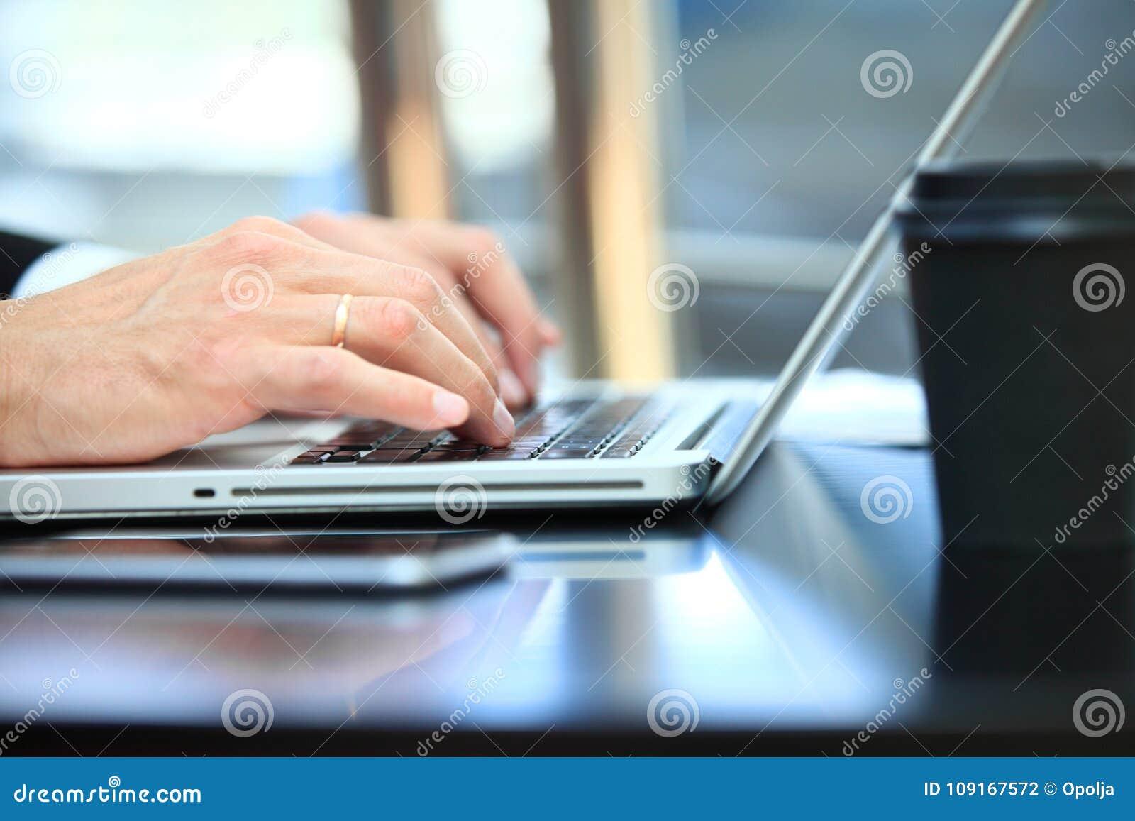 Plan rapproché de l homme d affaires de main à l aide de l ordinateur portable pour le travail au bureau