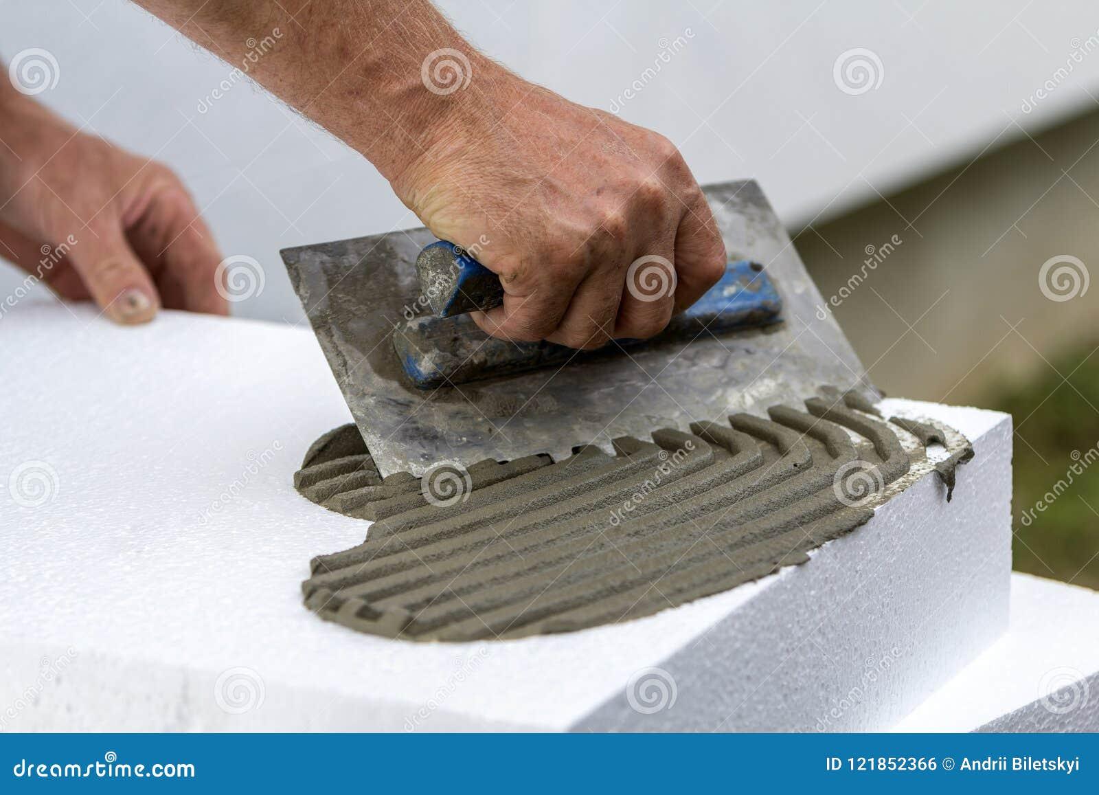 Plan rapproché de main de travailleur avec la truelle appliquant la colle sur la feuille rigide blanche de mousse de polyuréthane