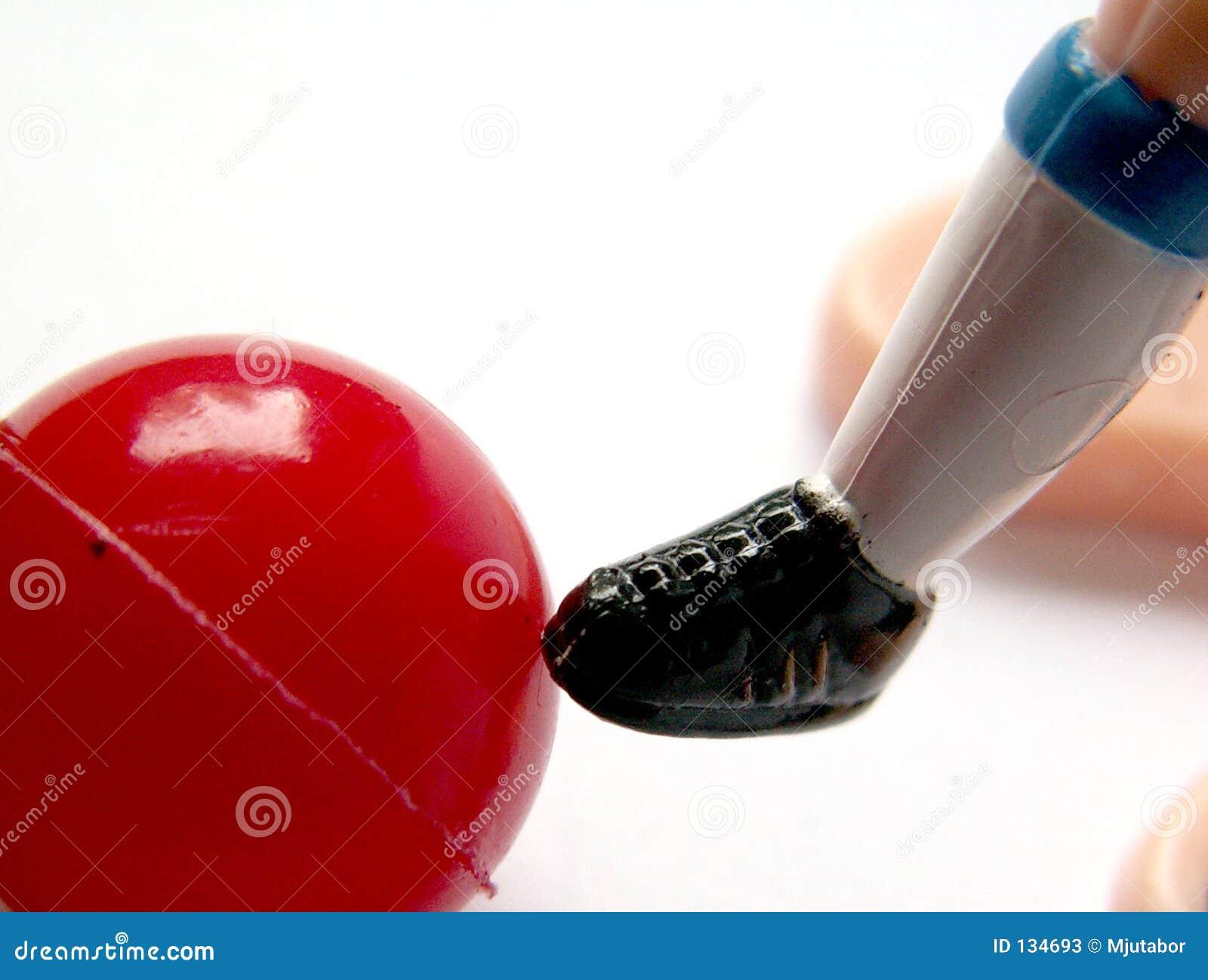 Plan rapproché de pied en plastique de footballeur de jouet avec la bille rouge