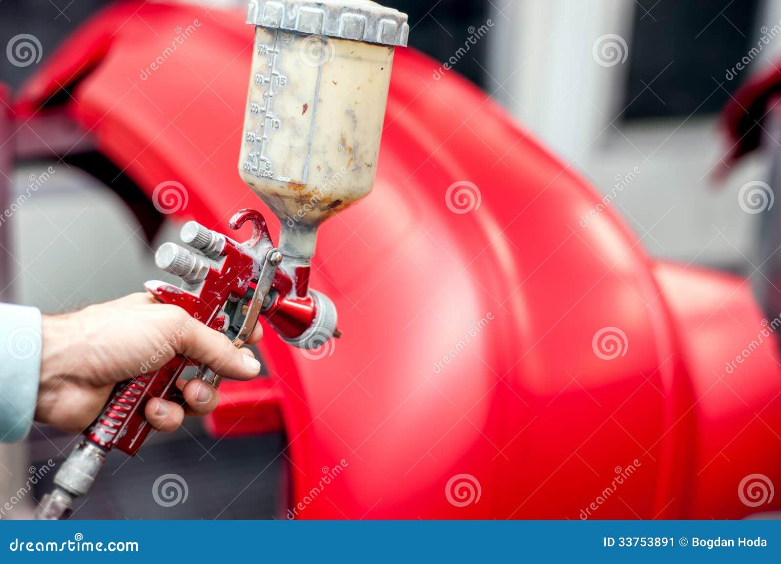 Plan rapproché de pistolet de pulvérisation avec la peinture rouge peignant une voiture