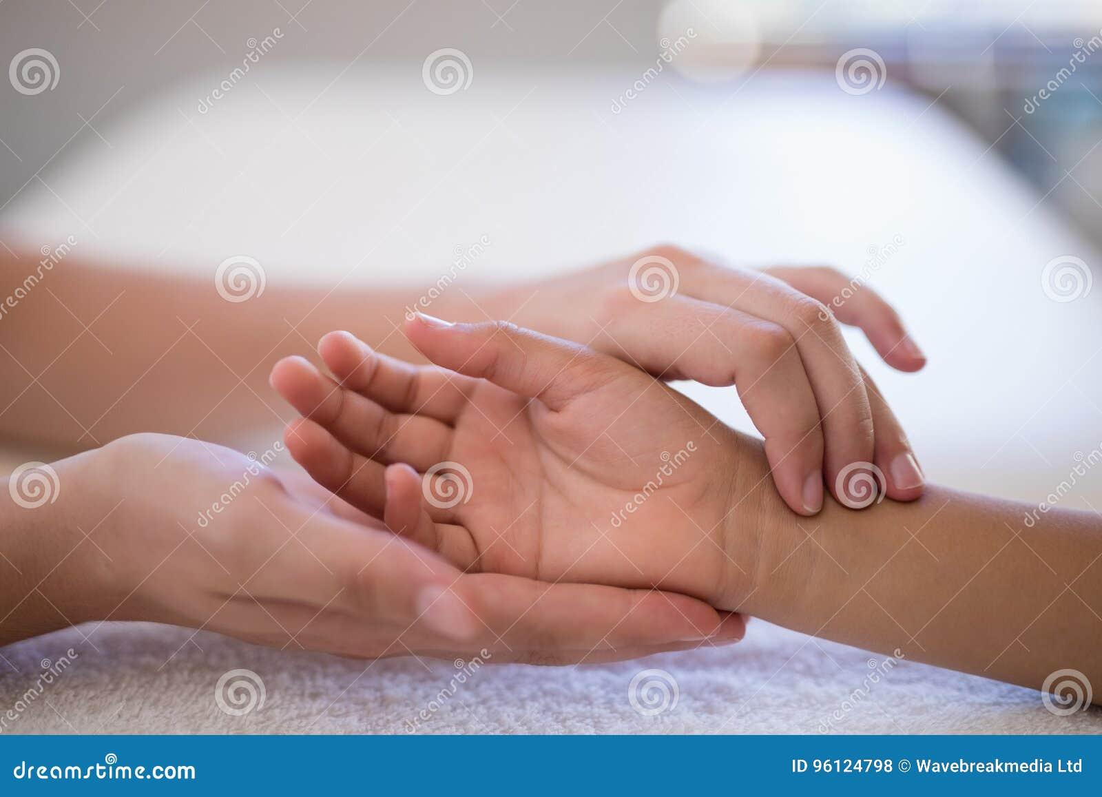Plan rapproché de poignet de examen de thérapeute féminin sur la serviette blanche