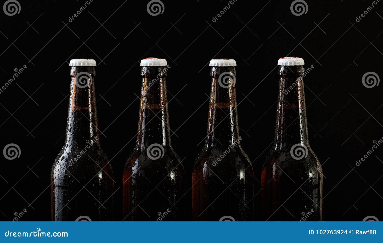 Plan rapproché de quatre bouteilles à bière d isolement sur le fond noir