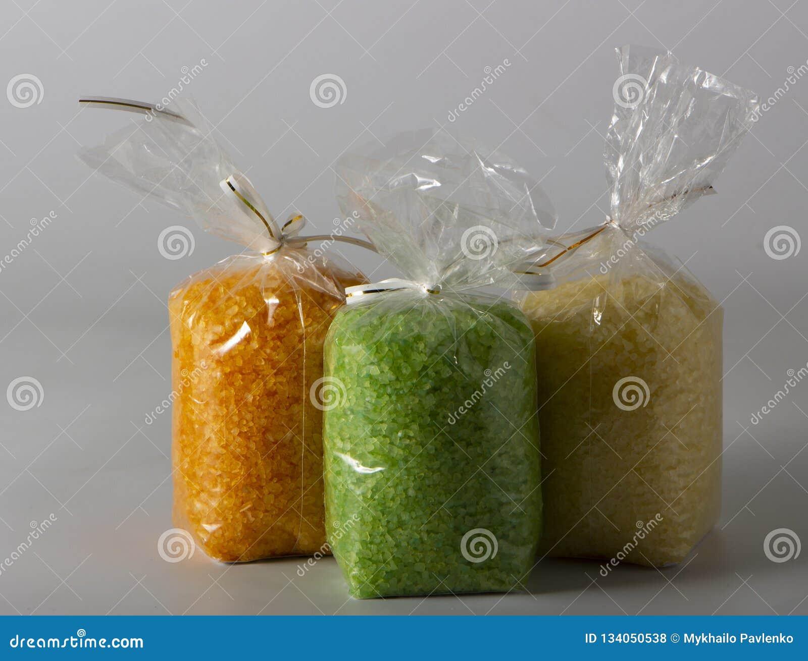 Plan rapproché de sel multicolore de mer dans des sachets en plastique sur le marché