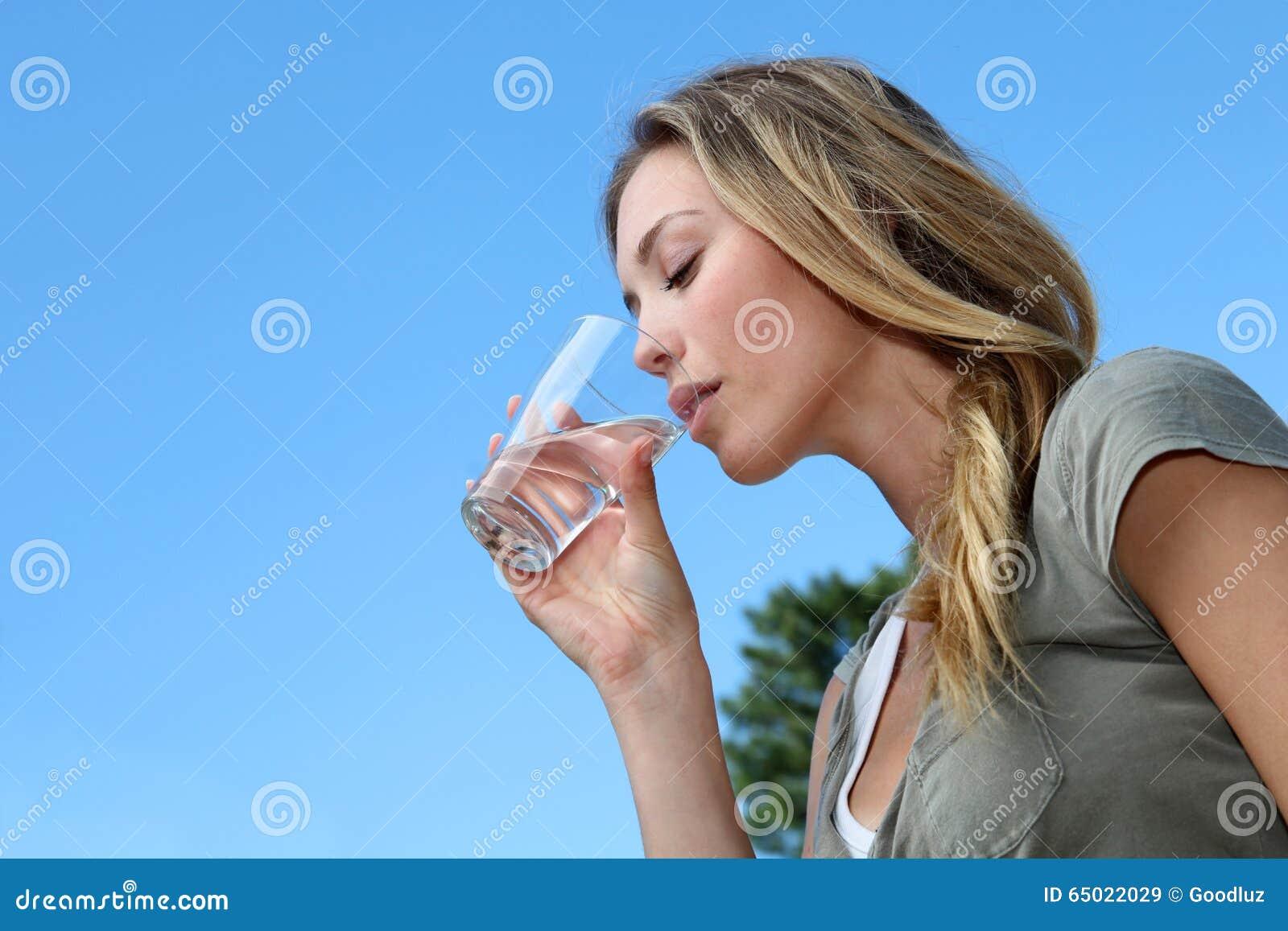 Plan rapproché de verre à boire blond de jeune femme de l eau