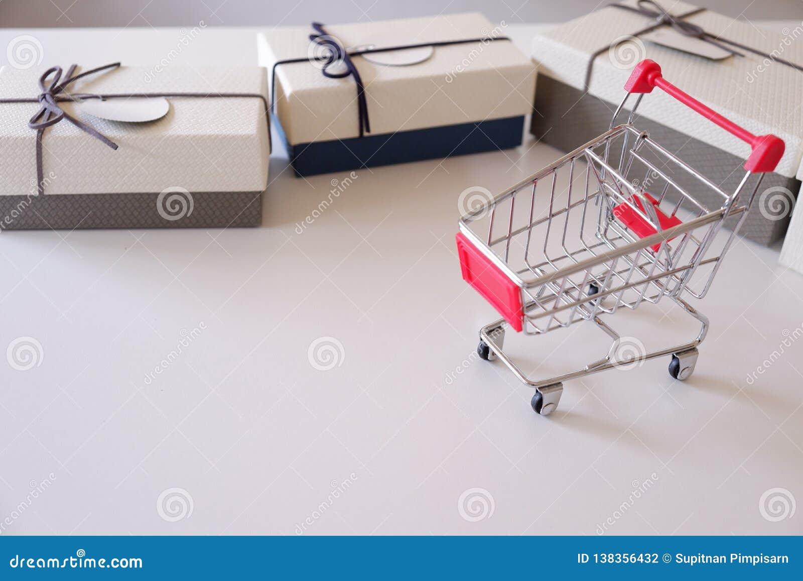 Plan rapproché des boîte-cadeau et du caddie sur le bureau blanc