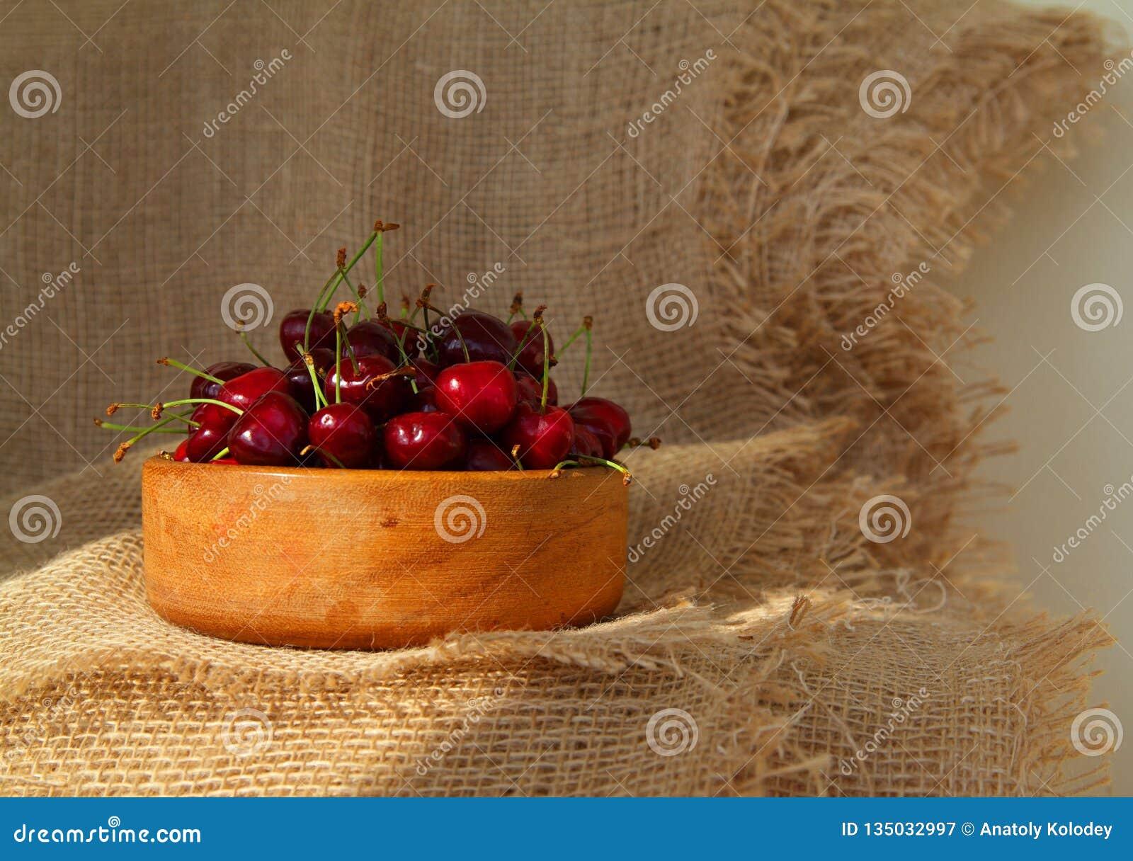 Plan rapproché des cerises savoureuses fraîches dans la cuvette en bois Dessert rustique de style
