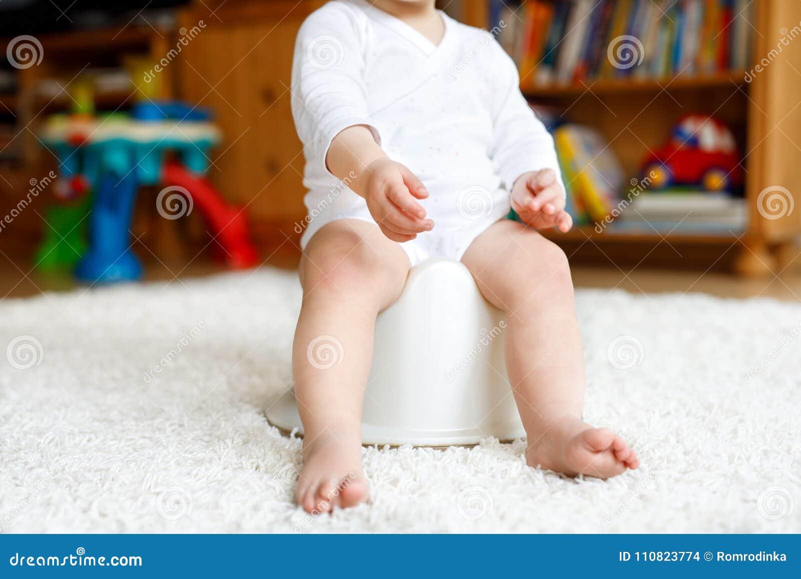 Plan rapproché des jambes de petits 12 mois mignons d enfant en bas âge d enfant de bébé s asseyant sur le pot