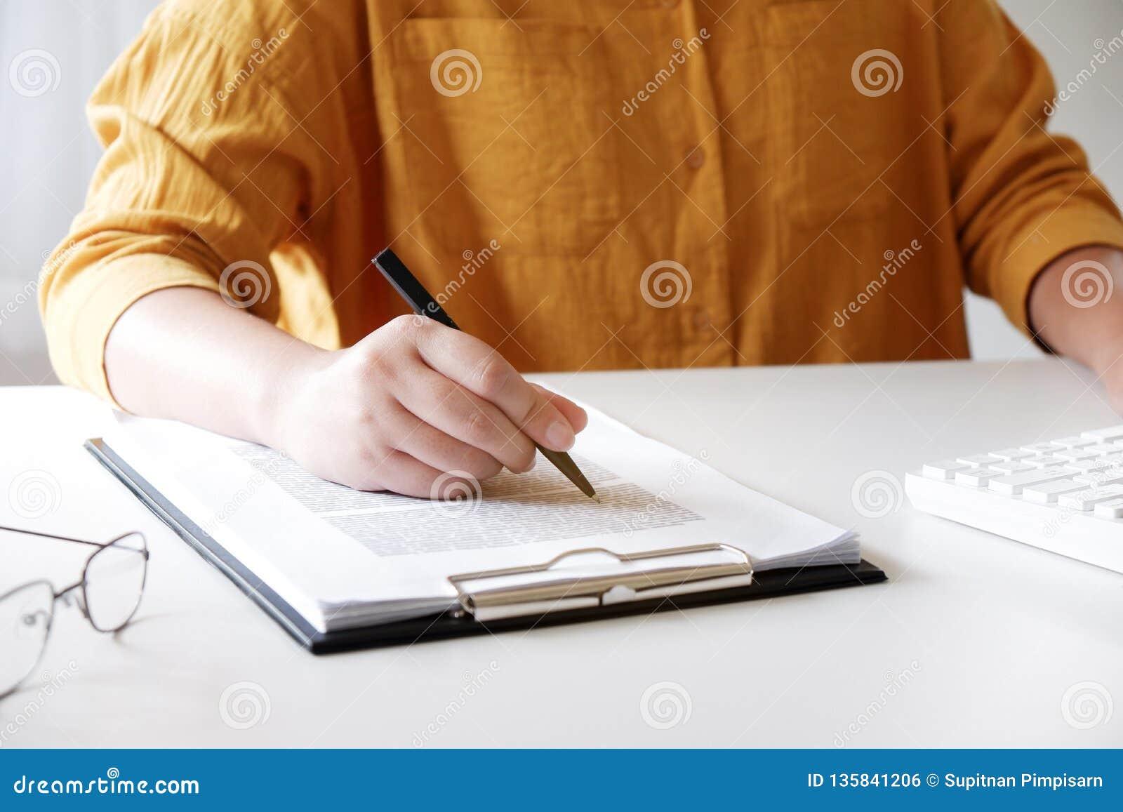 Plan rapproché des mains femelles inscription de quelque chose dans son bureau