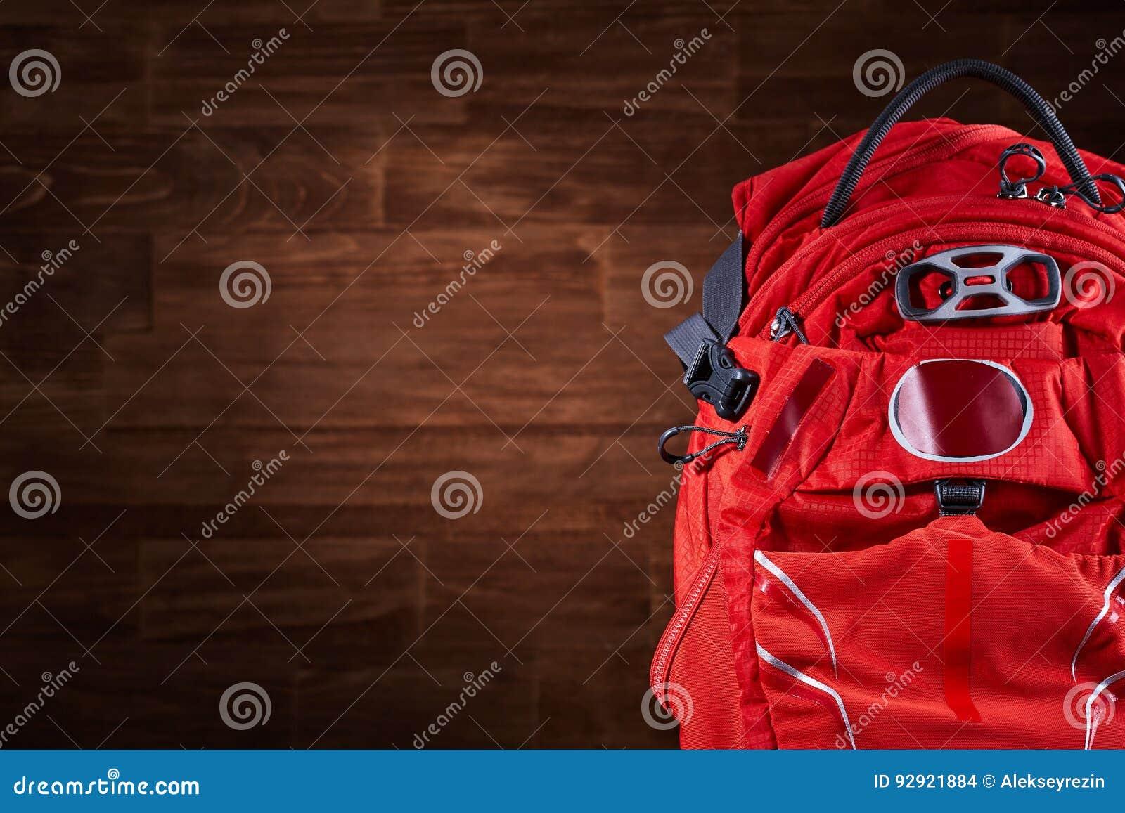 Plan rapproché du grand sac à dos orange de hausse sur le fond en bois