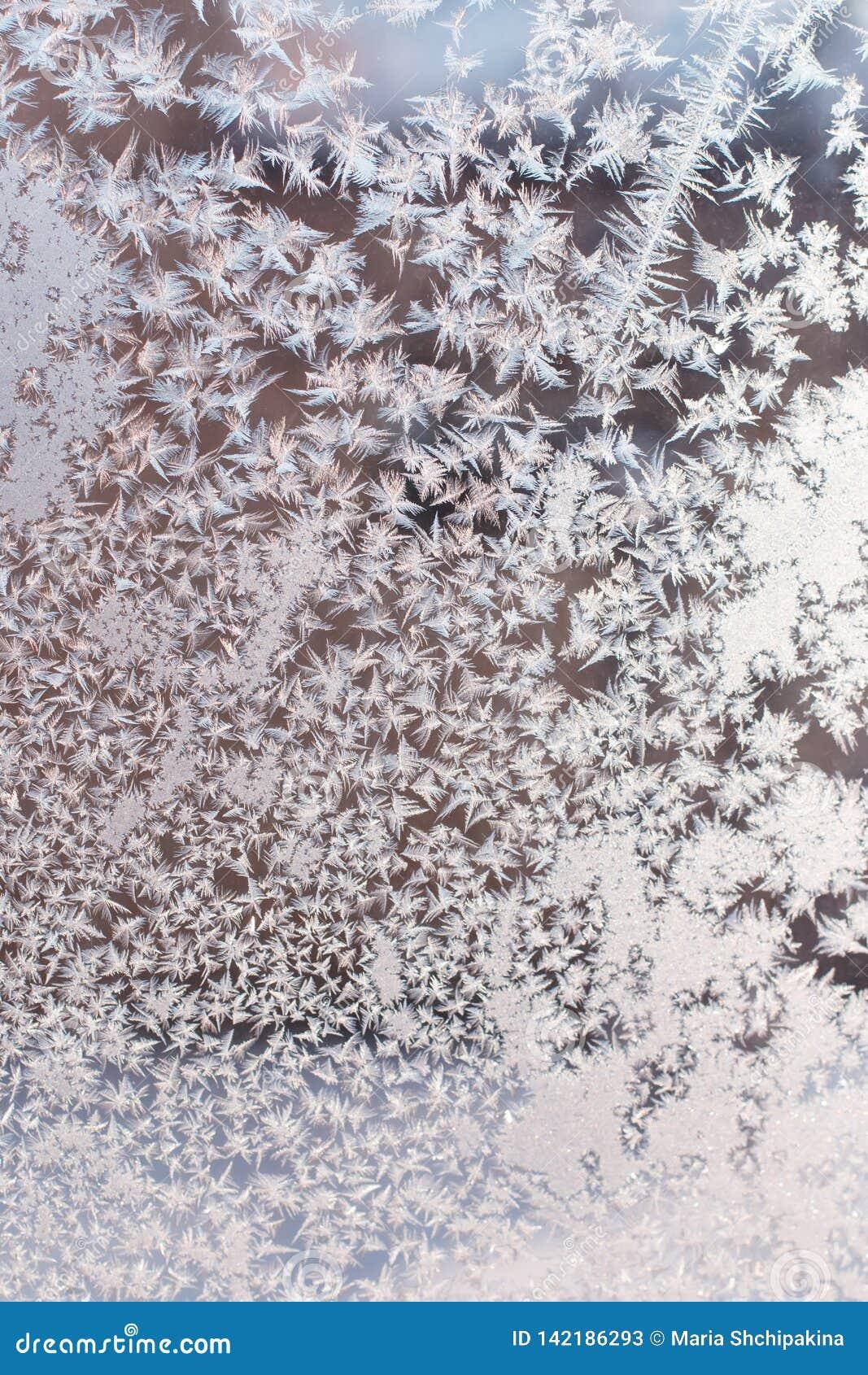 Plan rapproché en verre givré avec les cristaux lumineux, fond d hiver Gel sur l hublot
