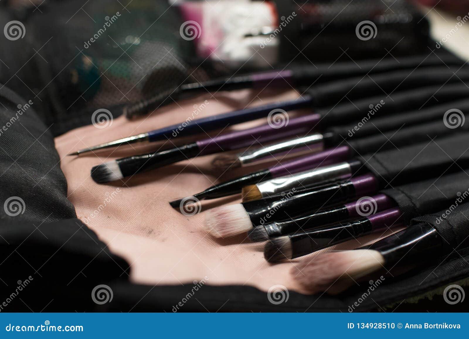 Plan rapproché professionnel de brosse de lecture de maquillage près de miroir de salon