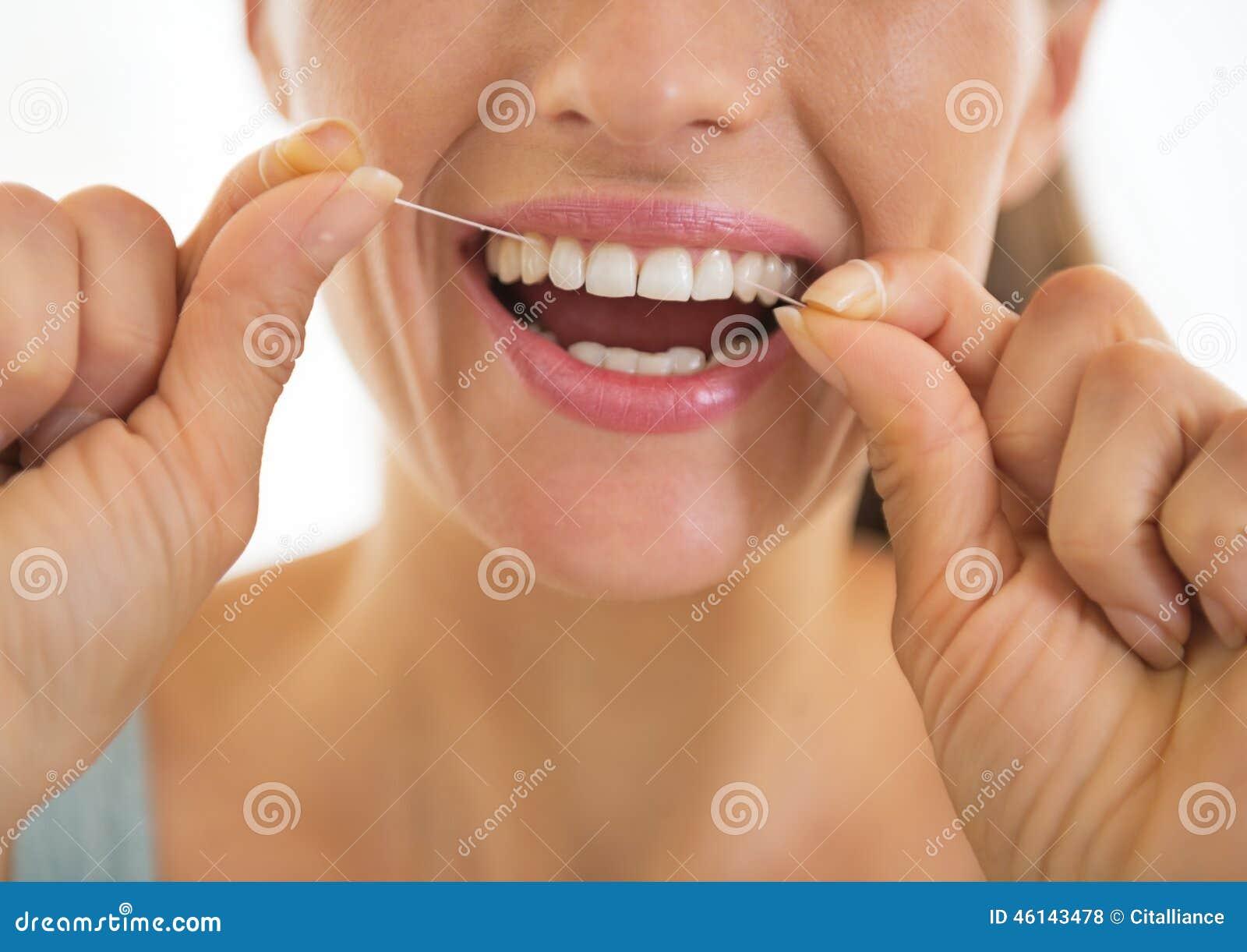 Plan rapproché sur la jeune femme employant le fil dentaire