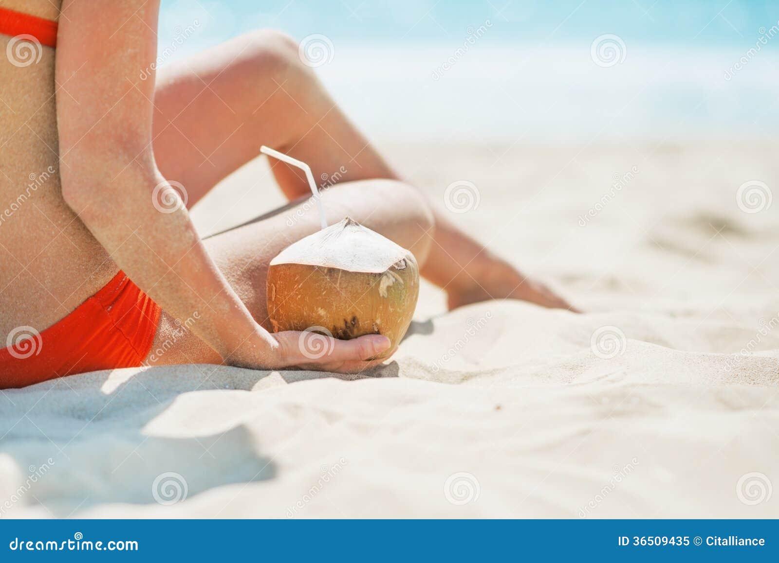 Plan rapproché sur la jeune femme s asseyant avec la noix de coco