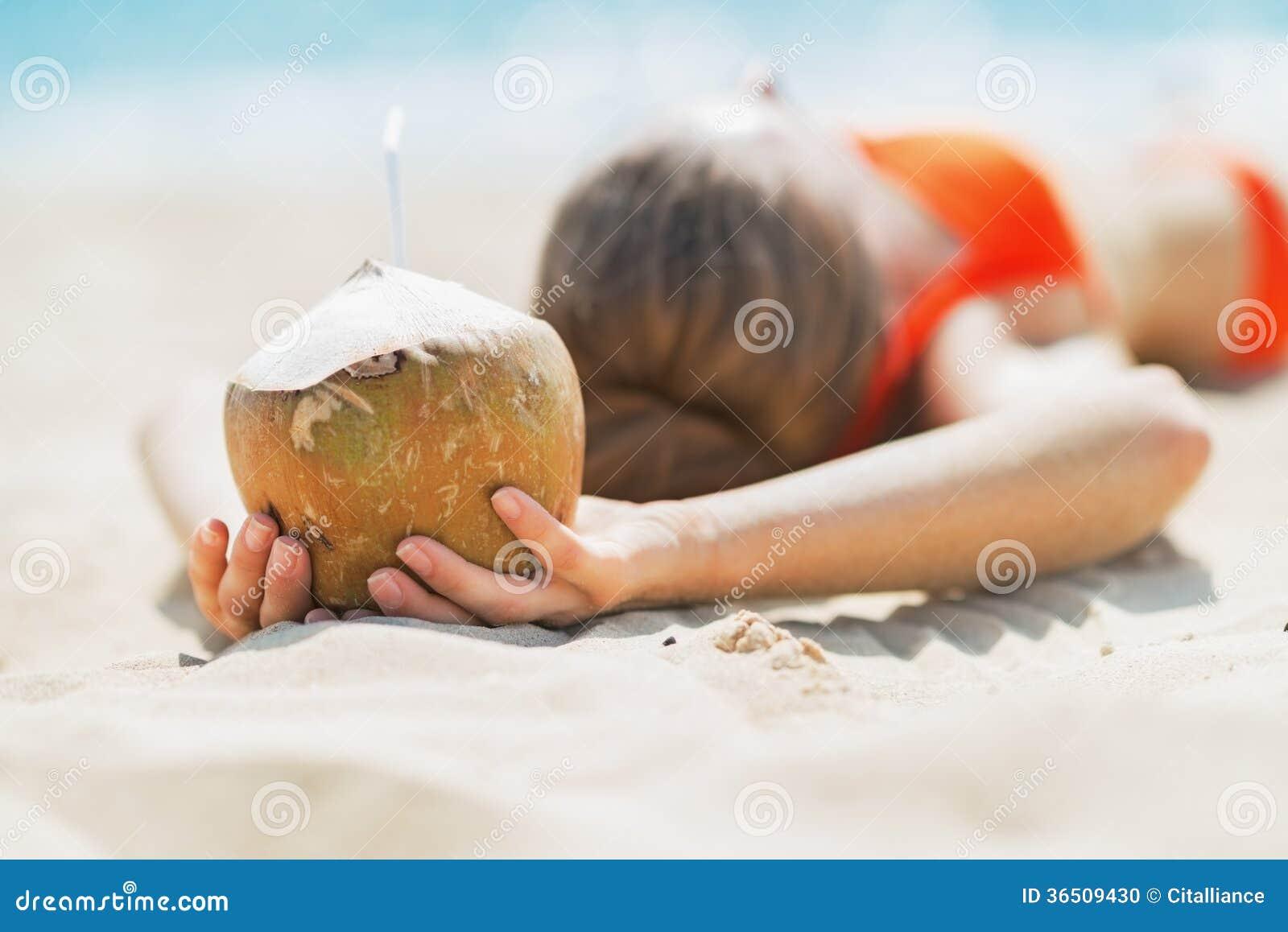 Plan rapproché sur la jeune femme tenant la noix de coco