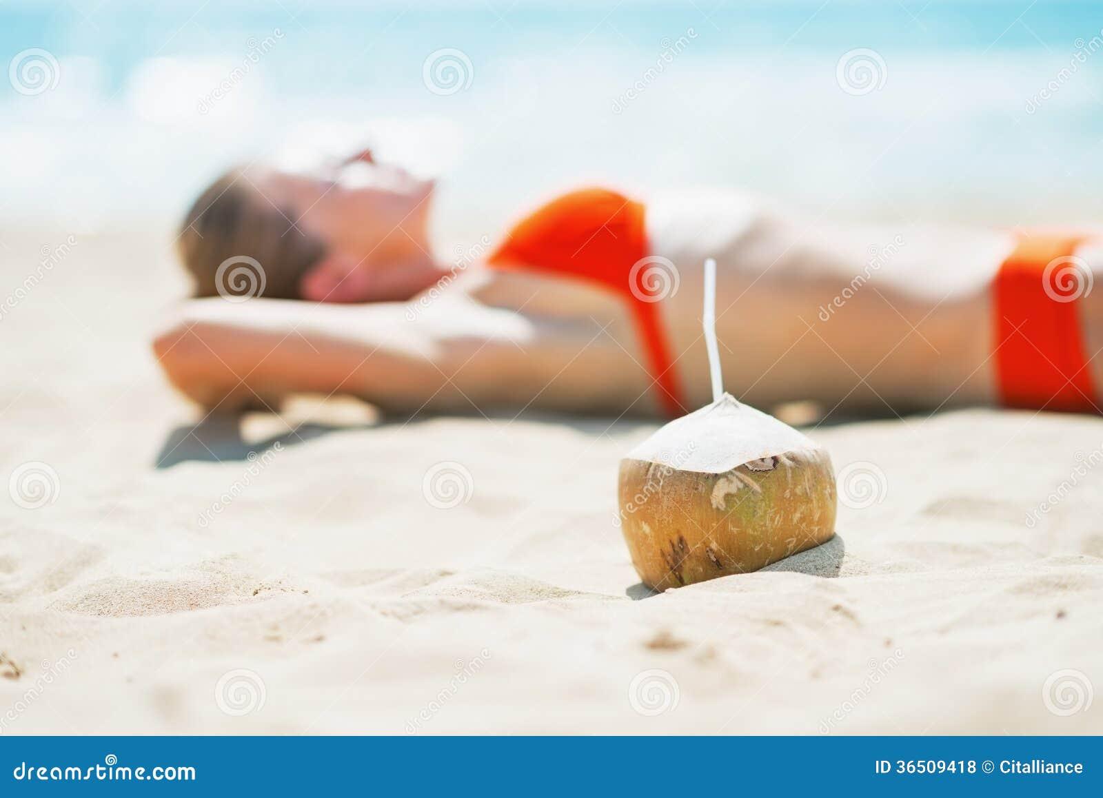 Plan rapproché sur la noix de coco et la jeune femme s étendant sur la plage à l arrière-plan