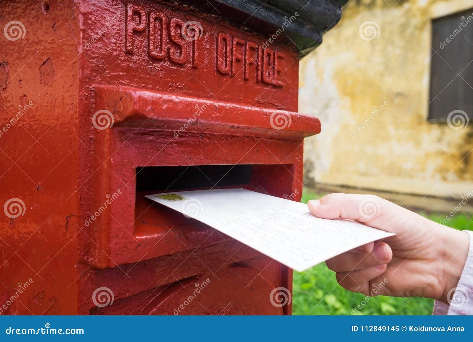Plan rapproché sur une main masculine mettant une lettre dans une boîte à marquer d une pierre blanche Concept de type de vintage