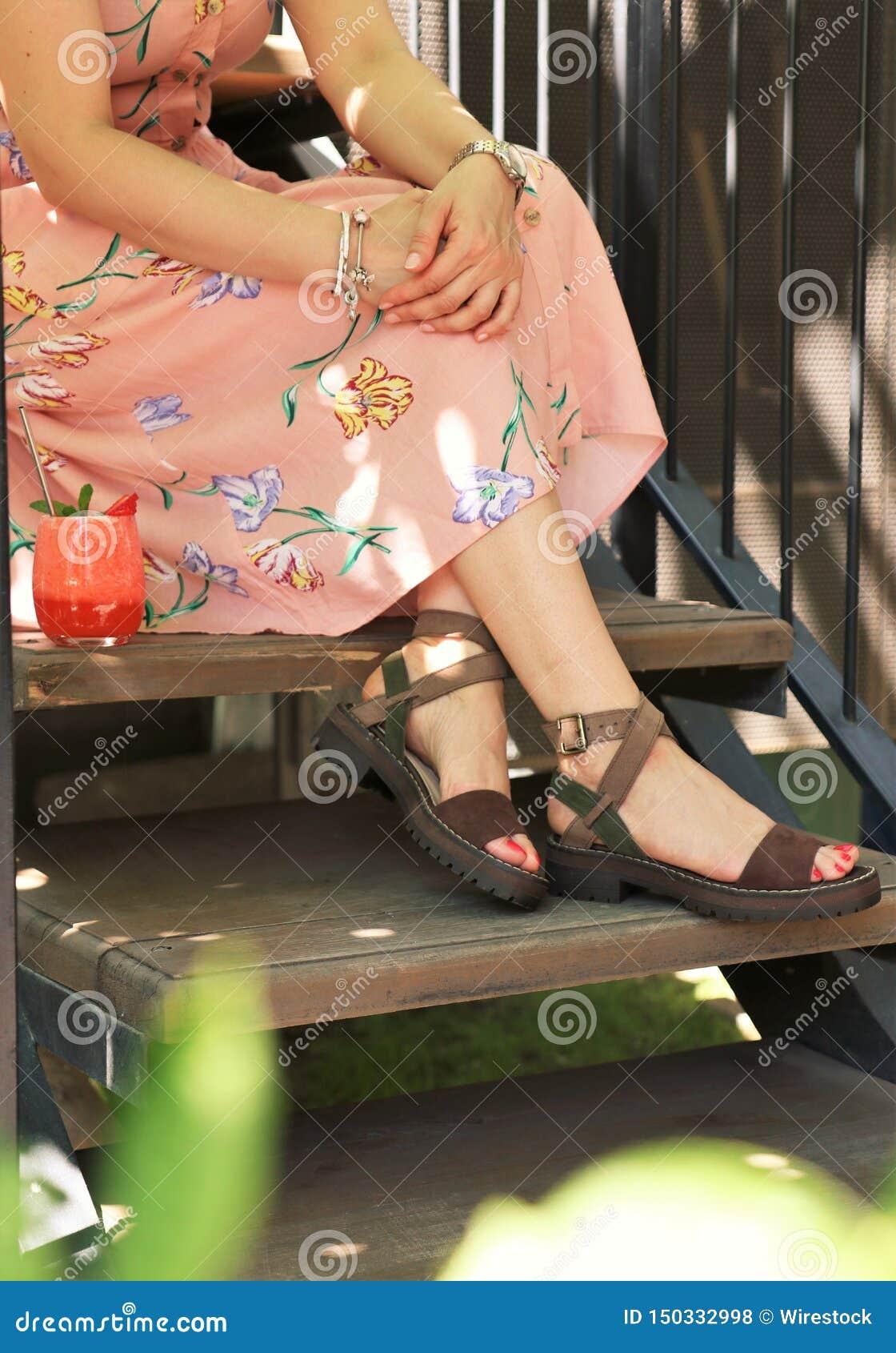 Plan rapproché tiré des pieds élégants d une femelle portant une robe à l été