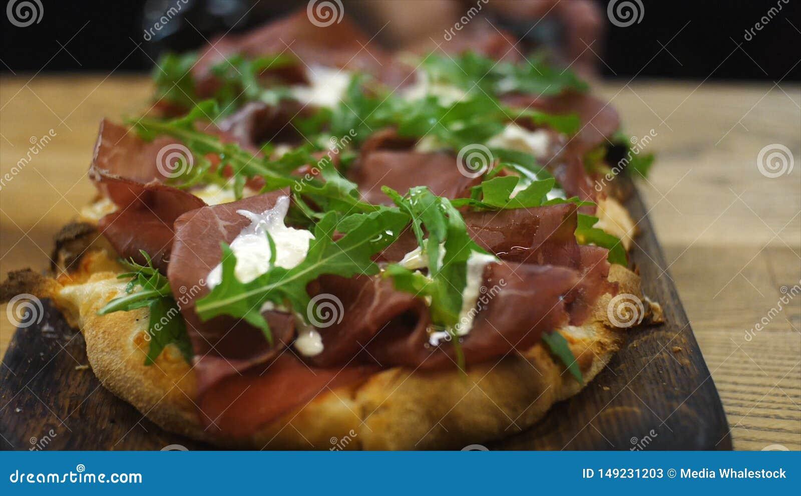 Plan rapproch? de petite pizza italienne d?licieuse avec le fromage de salade, de lard et fondu s ?tendant sur une pelle en bois