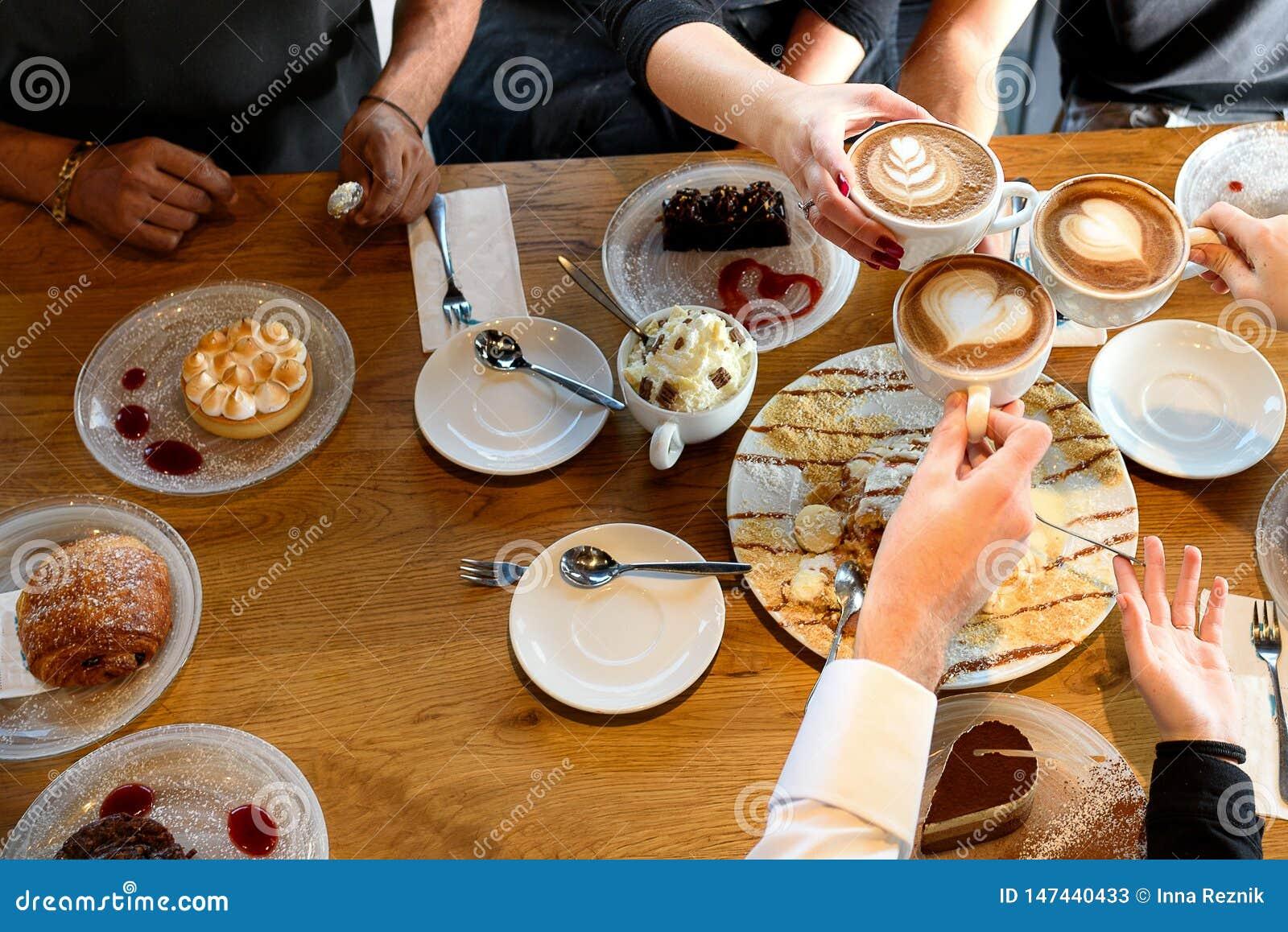 Plan rapproch? des mains avec des desserts et des tasses de caf? dans un caf?