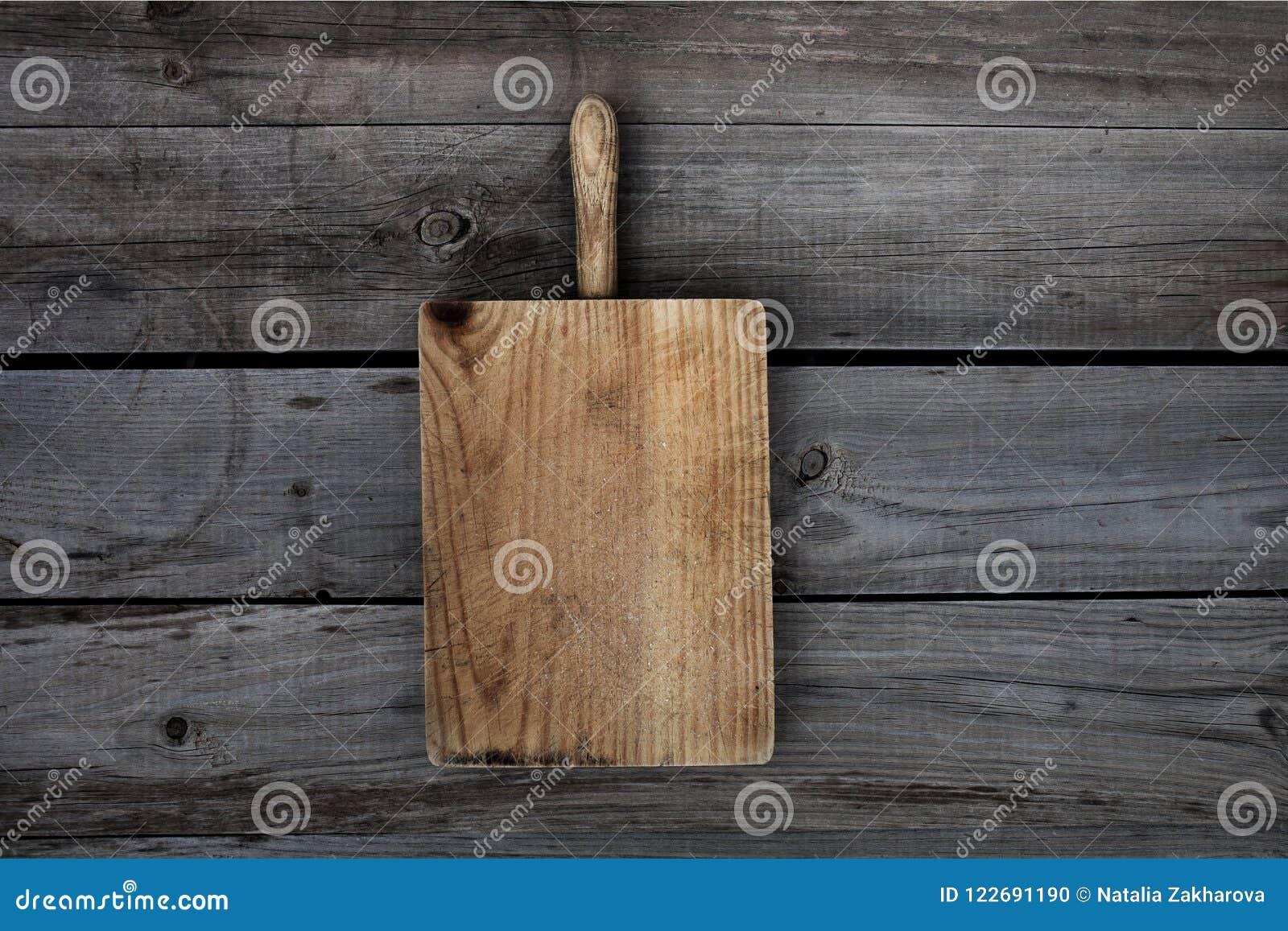 Planche à découper en bois sur le fond foncé vieux bureau grunge
