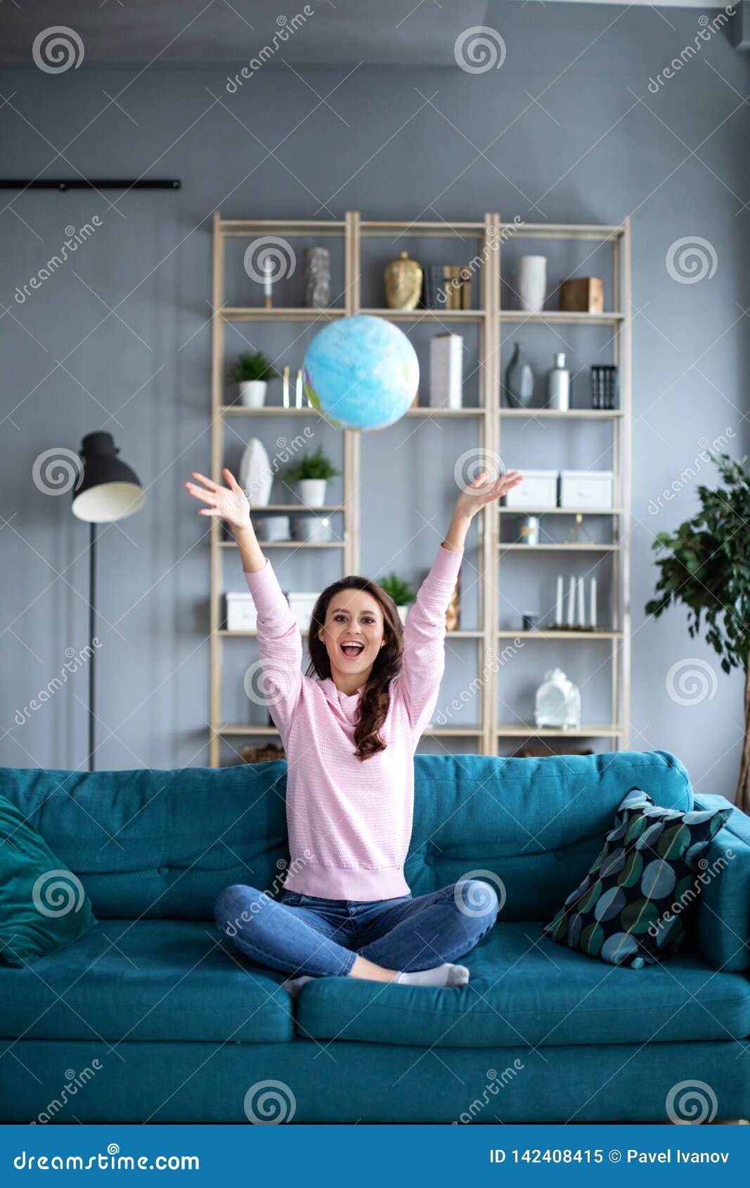 Planeamiento joven acertado jubiloso a las vacaciones con el globo del mundo