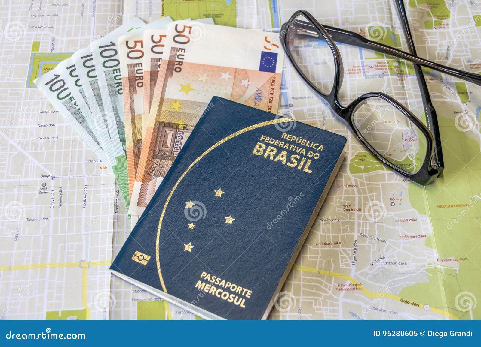 Planeando un viaje - el pasaporte brasileño en mapa de la ciudad con euro carga en cuenta el dinero y los vidrios