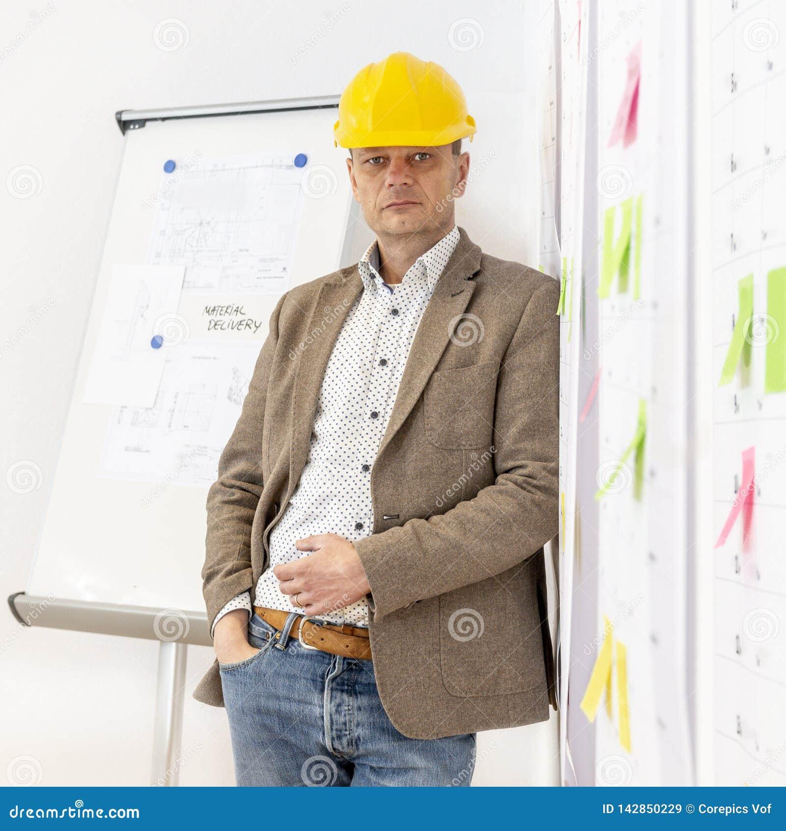 Planer, der an einer Wand mit Planungsdetails sich lehnt