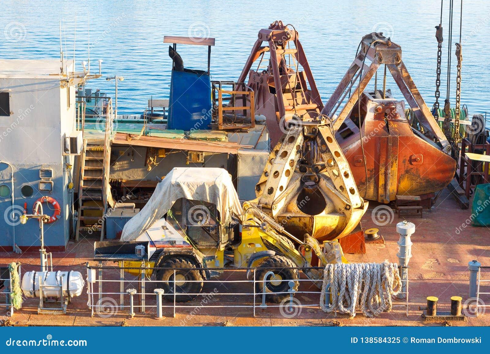 Planierraupe und rostige Schaufel des Frachtkranes auf der Schiffsplattform