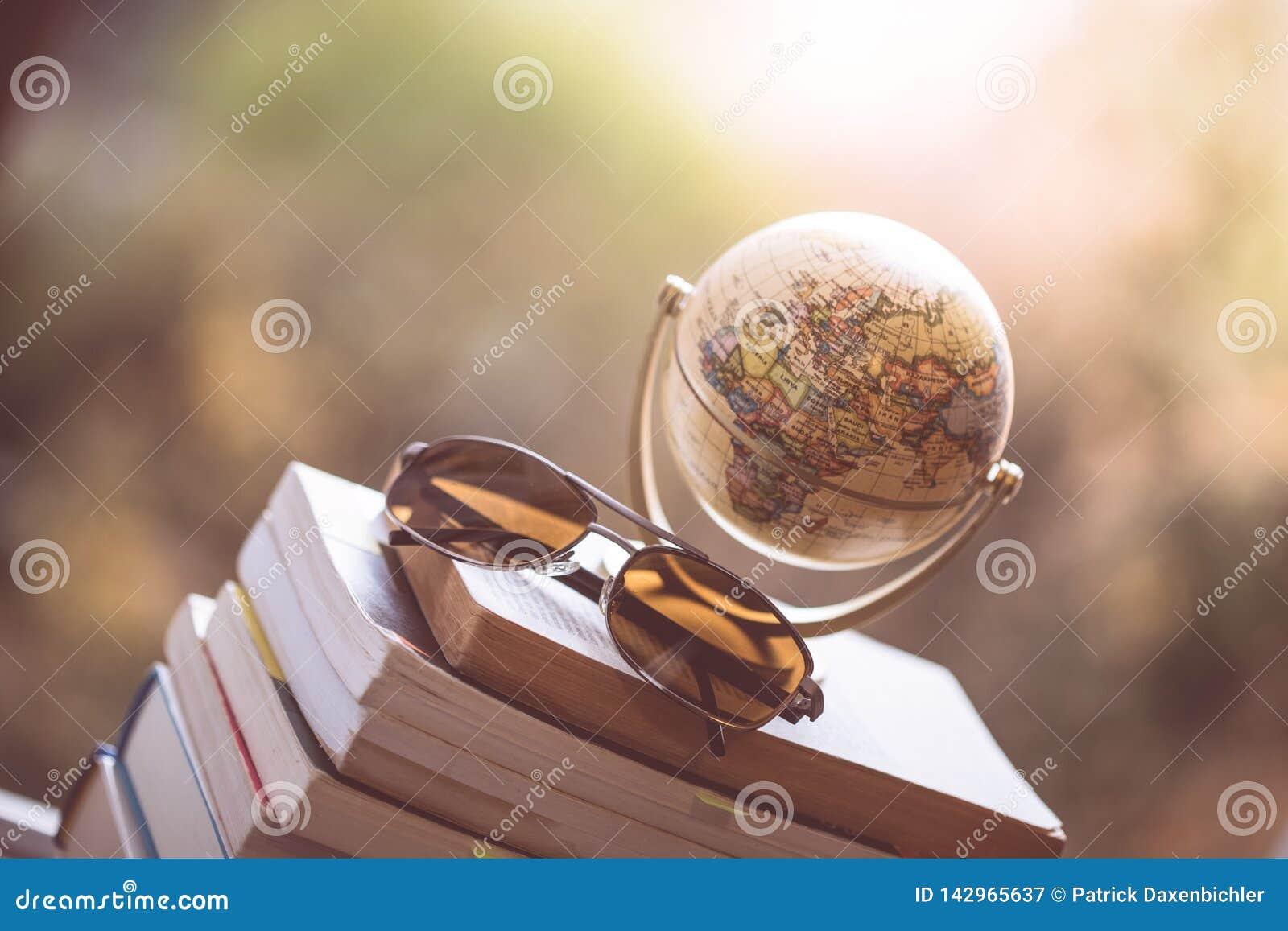 Planificación del viaje siguiente: Globo y gafas de sol miniatura en una pila de libros