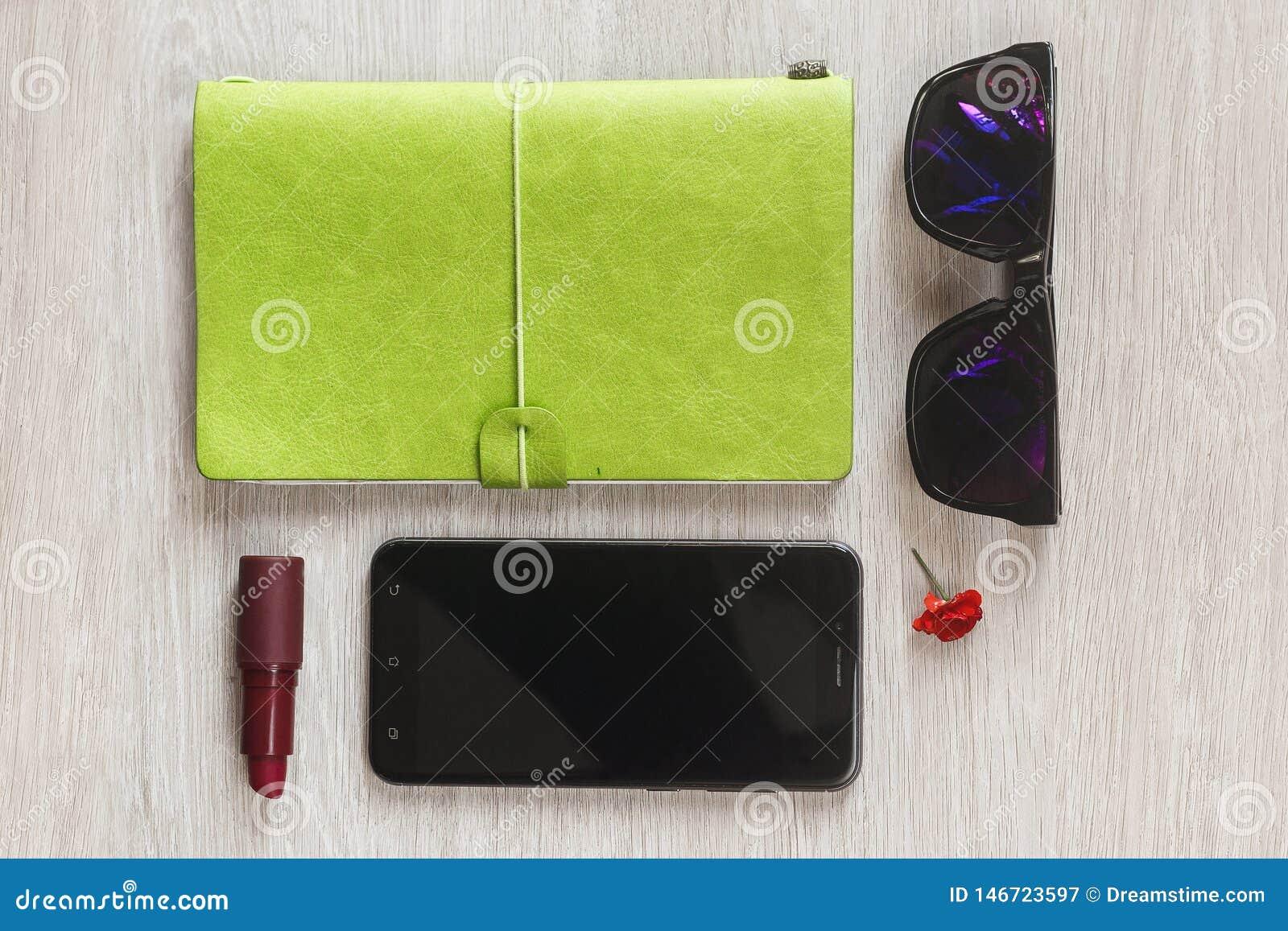 Planificador del cuaderno, tel?fono m?vil y bolso rosado de la trabajadora de la forma de vida para el negocio en el escritorio d