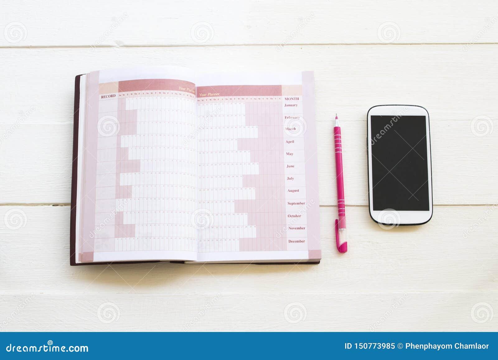 Planificador del cuaderno y tel?fono m?vil para el trabajo del negocio