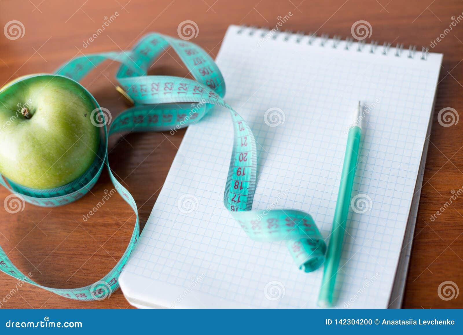 Planification d un régime Un carnet c une inscription - le régime, une bande de mesure, une pomme et stylo