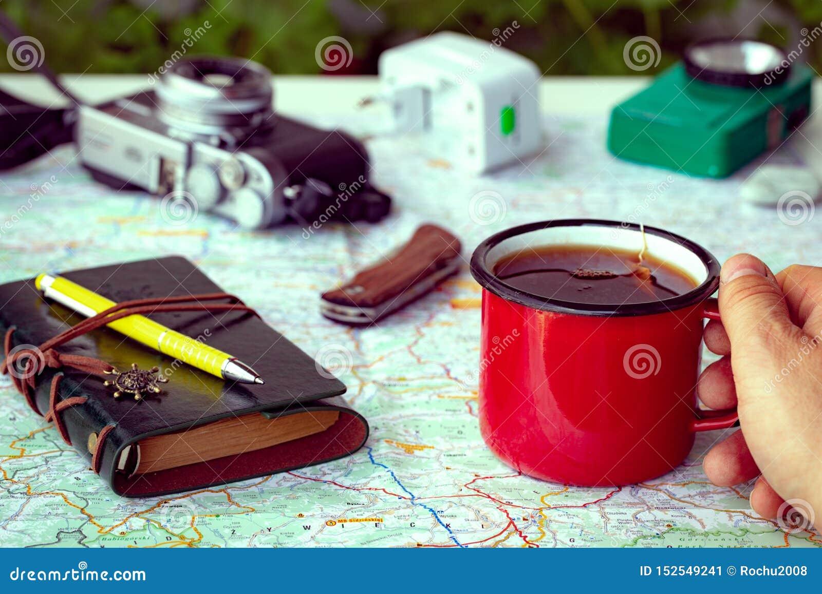 Planification d un voyage avec une carte à côté d une tasse de thé et d équipement campant