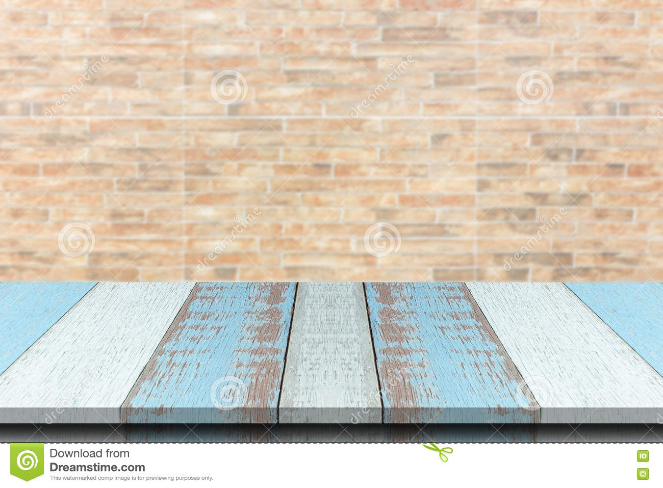 Plank wood or table top with blurred synthetic wall brick background.