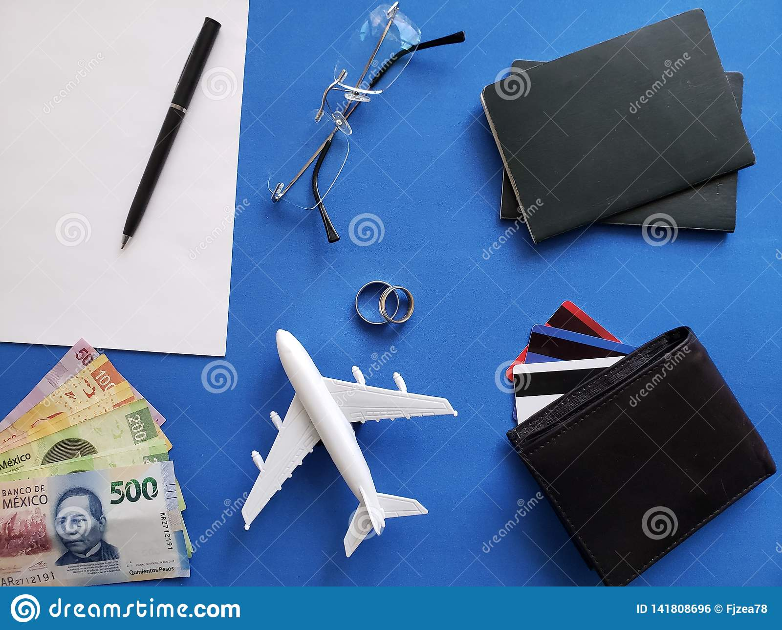 planning the honeymoon trip, rings, eyeglasses, mexican banknotes, passports, credit cards and figure of an airplane, top view