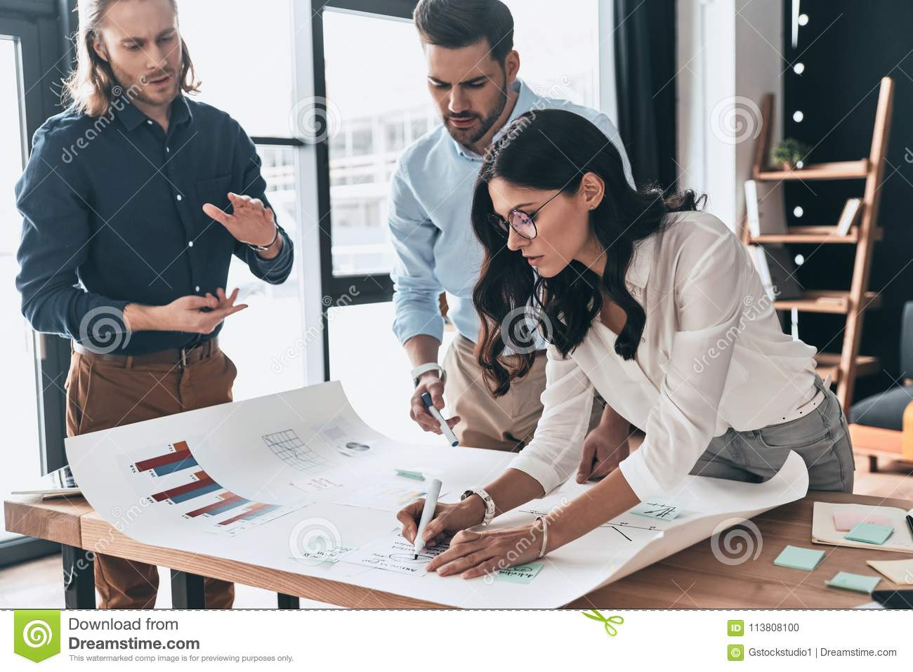 Planning new business strategy. Group of young confident business people discussing something while woman writing on blueprint in
