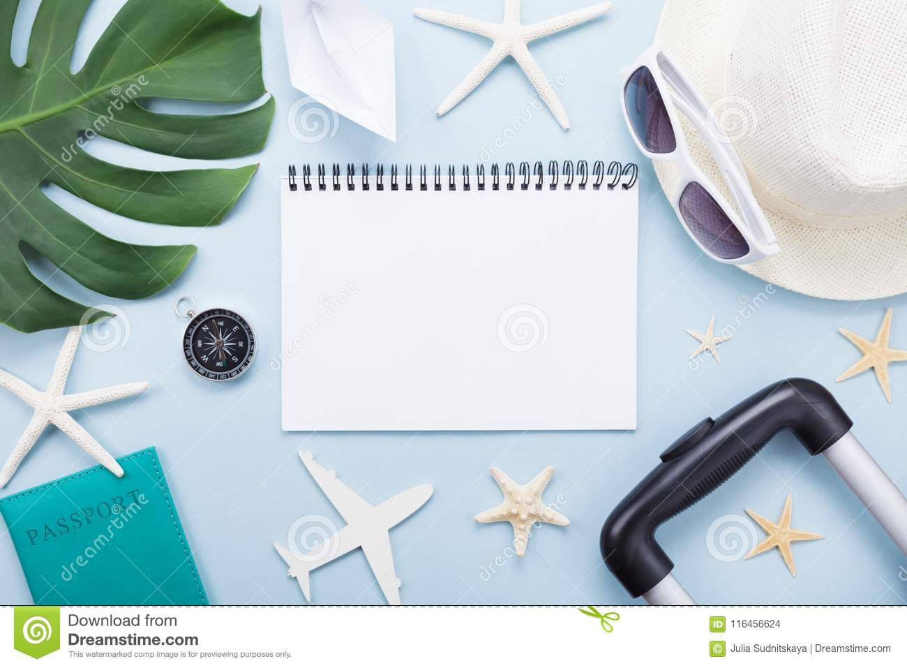 Planning summer holidays, vacations and trip. Travelers notebook with tourism accessories on blue table top view. Flat lay.