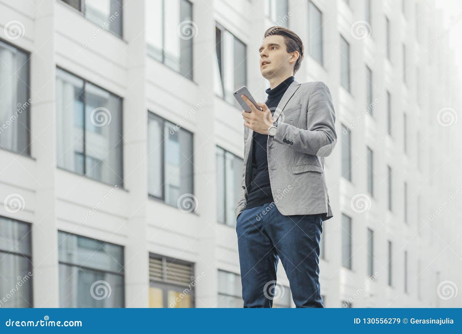 Plano distante do homem de negócios novo que fala pelo telefone celular ao lado do arranha-céus