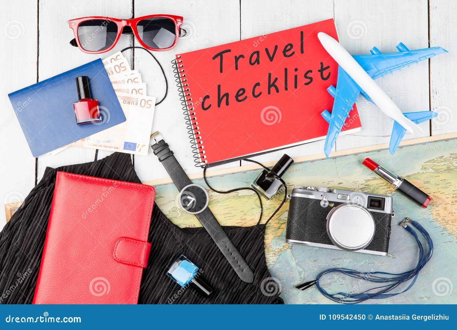 Plano, mapa, passaporte, dinheiro, relógio, câmera, bloco de notas com texto & x22; Checklist& x22 do curso; , óculos de sol, car