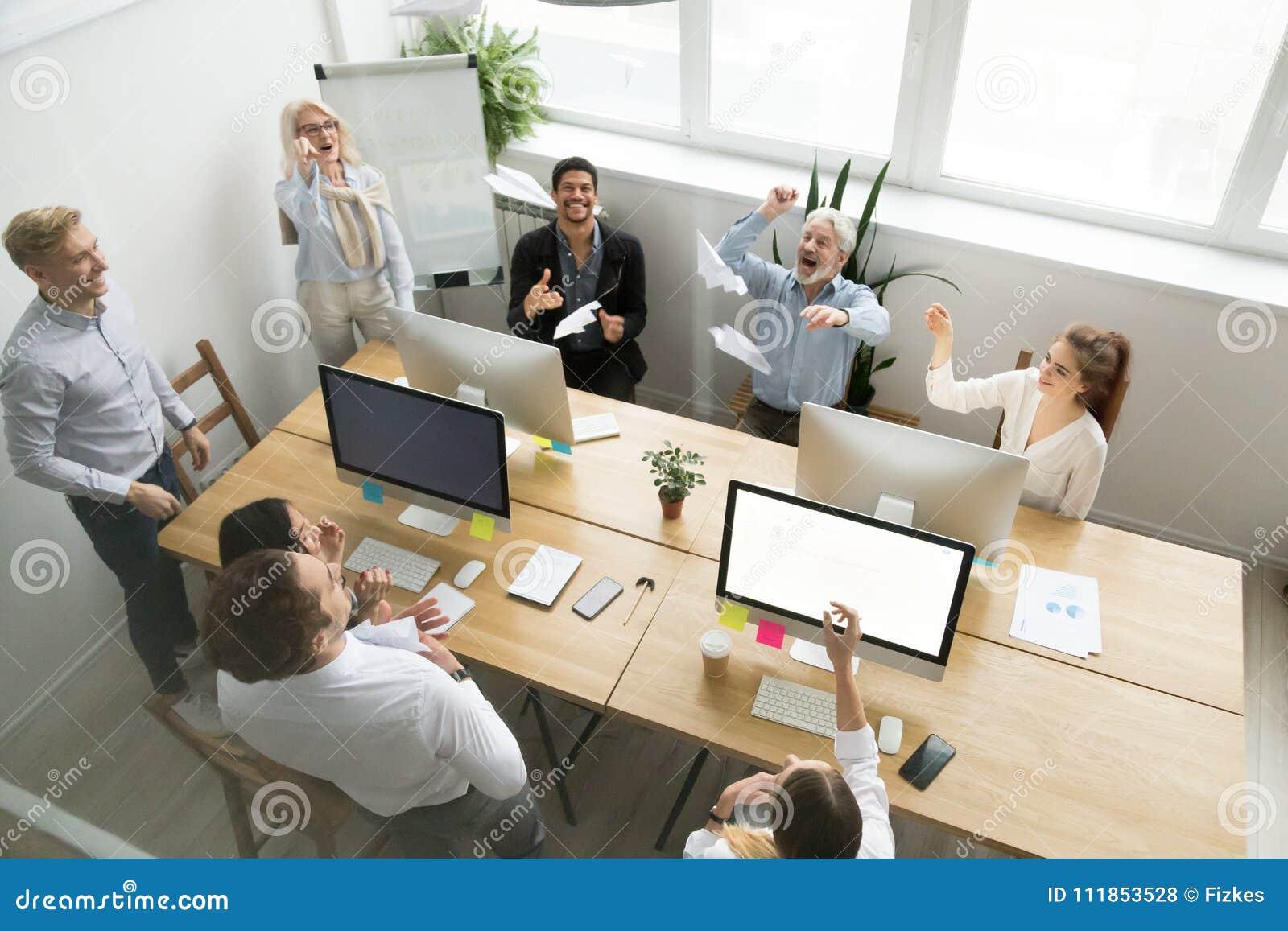Planos de papel de lançamento da equipe feliz diversa do escritório junto, v superior