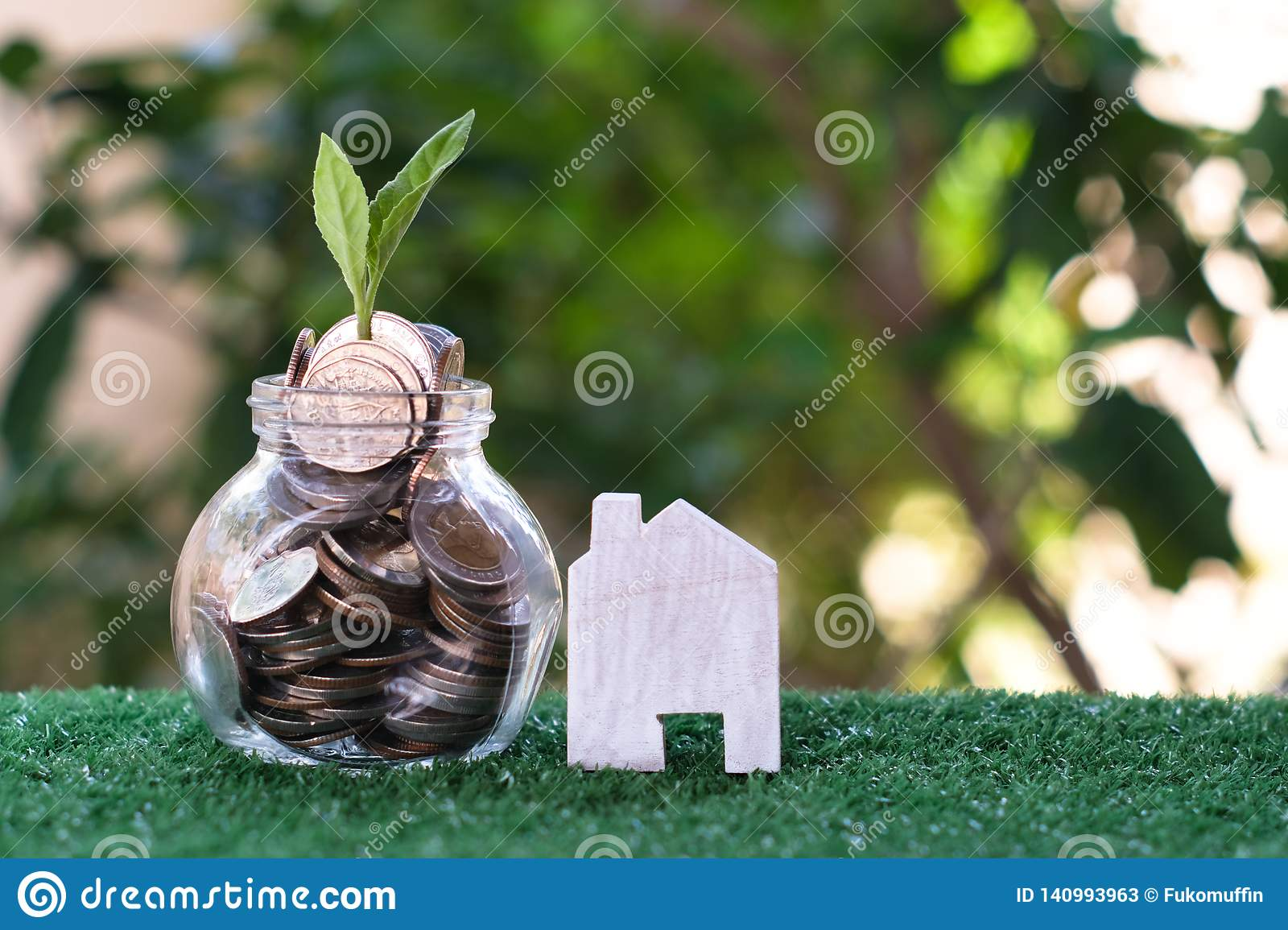 Plant growing from coins in glass jar. Wooden house model on artificial grass. Home mortgage and property investment concept