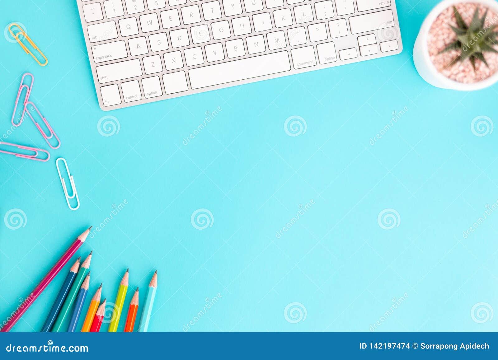 Plant lekmanna- foto av kontorsskrivbordet med blyertspennan och tangentbordet, workpace för bästa sikt på blå bakgrund och kopie