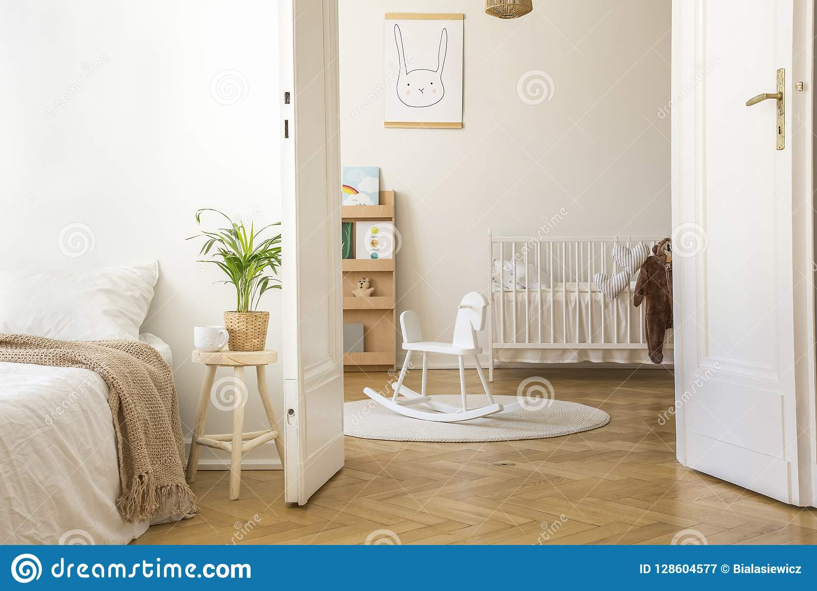 Plant on stool next to bed in white bedroom interior with rocking horse on rug and cradle