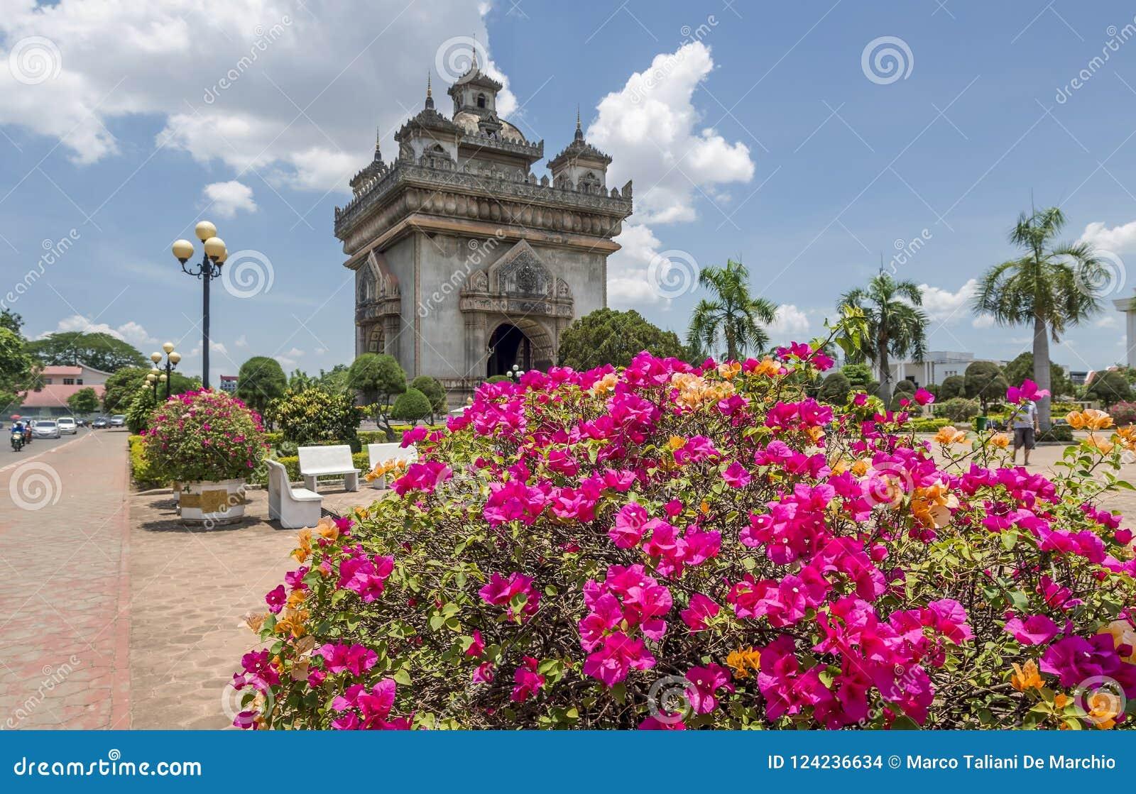 Planta bonita da buganvília com Victory Gate Patuxai no fundo no centro de Vientiane, Laos