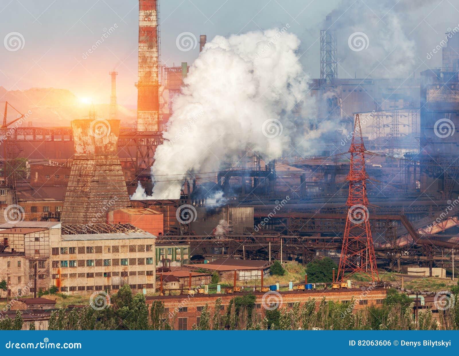 Planta de la metalurgia en Ucrania en la puesta del sol Fábrica de acero con niebla con humo