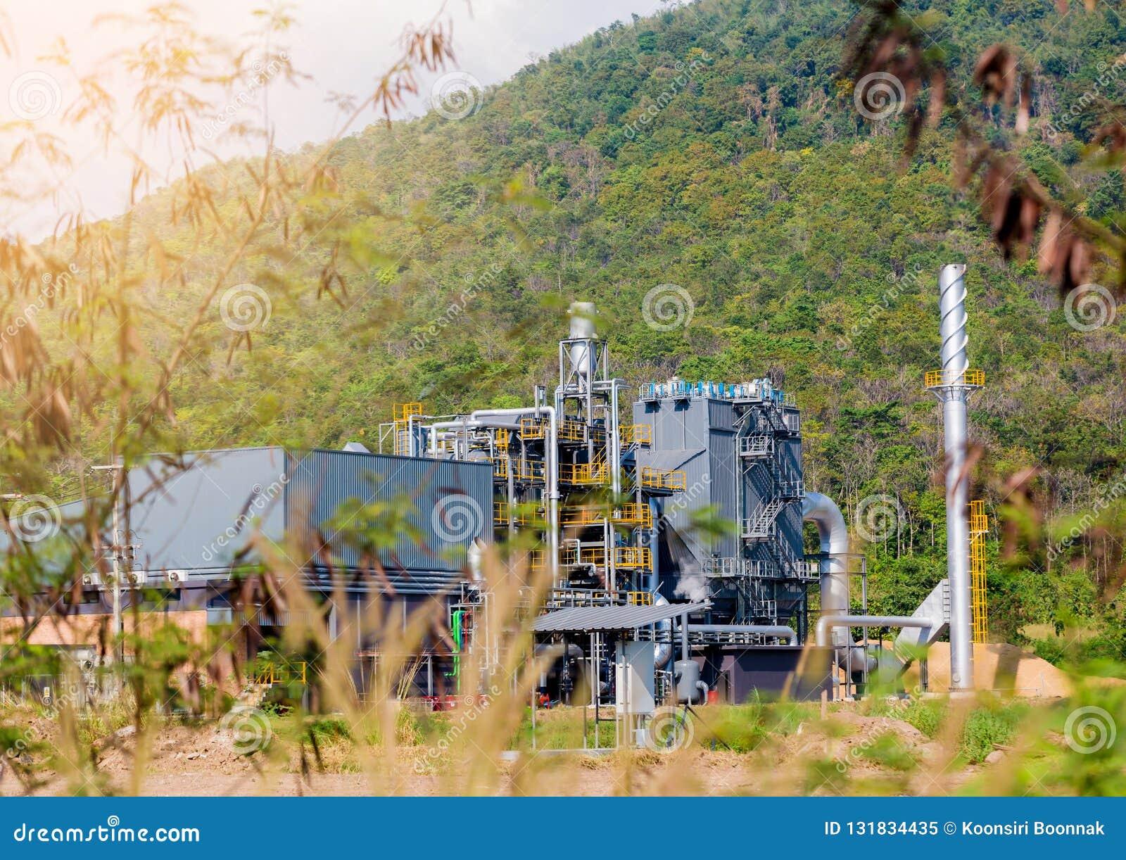 Planta industrial na área verde da árvore e de montanha