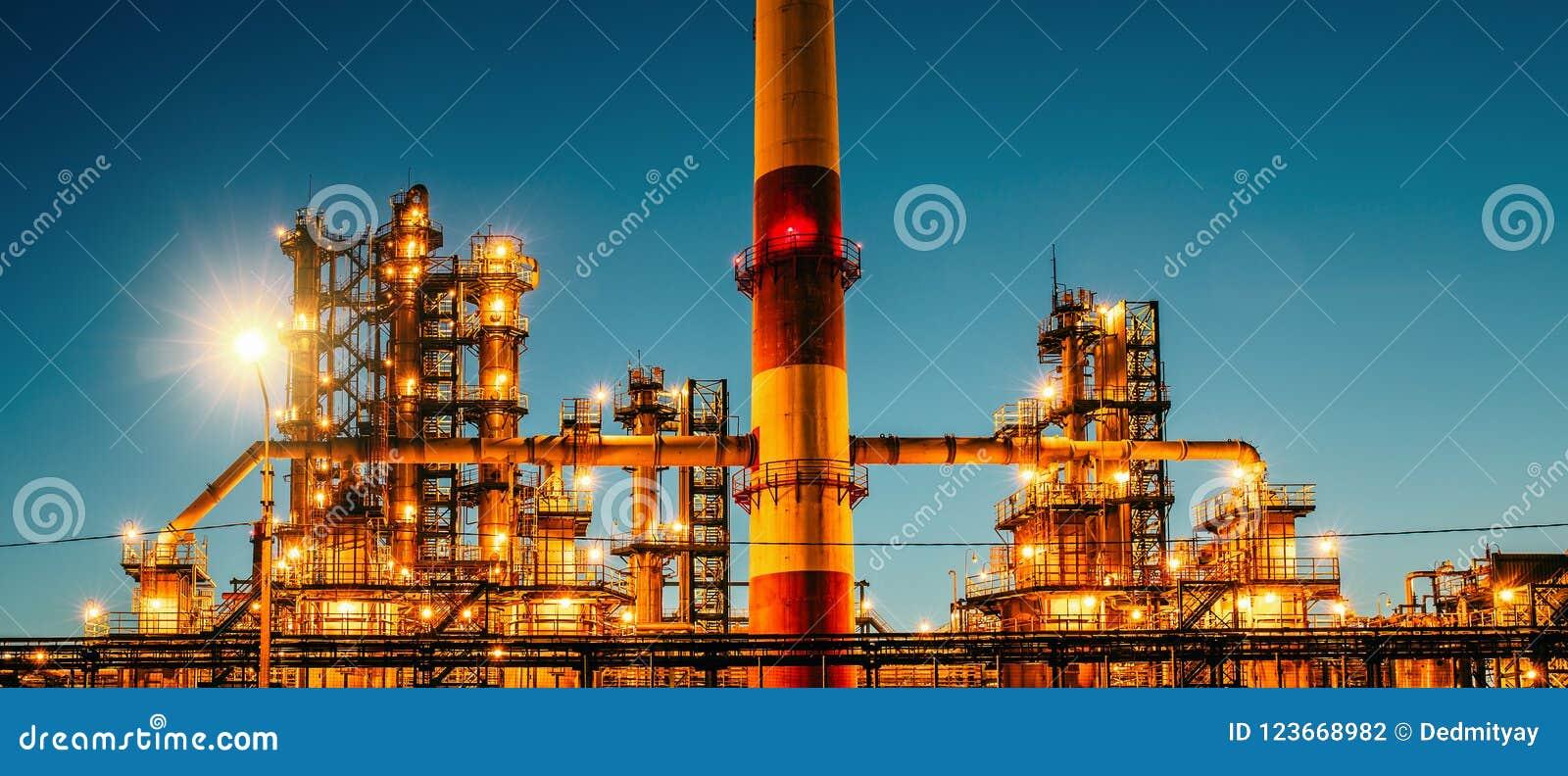 Planta industrial ou fábrica da refinaria de petróleo no por do sol, nos tanques da destilaria do armazenamento e no encanamento